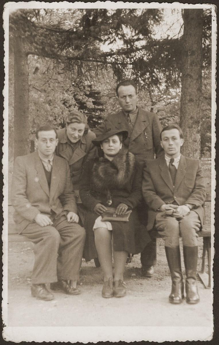 Group portrait of Jewish survivors in Bedzin, Poland.    Seated in the front row, from left are: Majer Fiszel; Lola (Merin) Laskier, and Heniek Fiszel.  The other two are not identified.