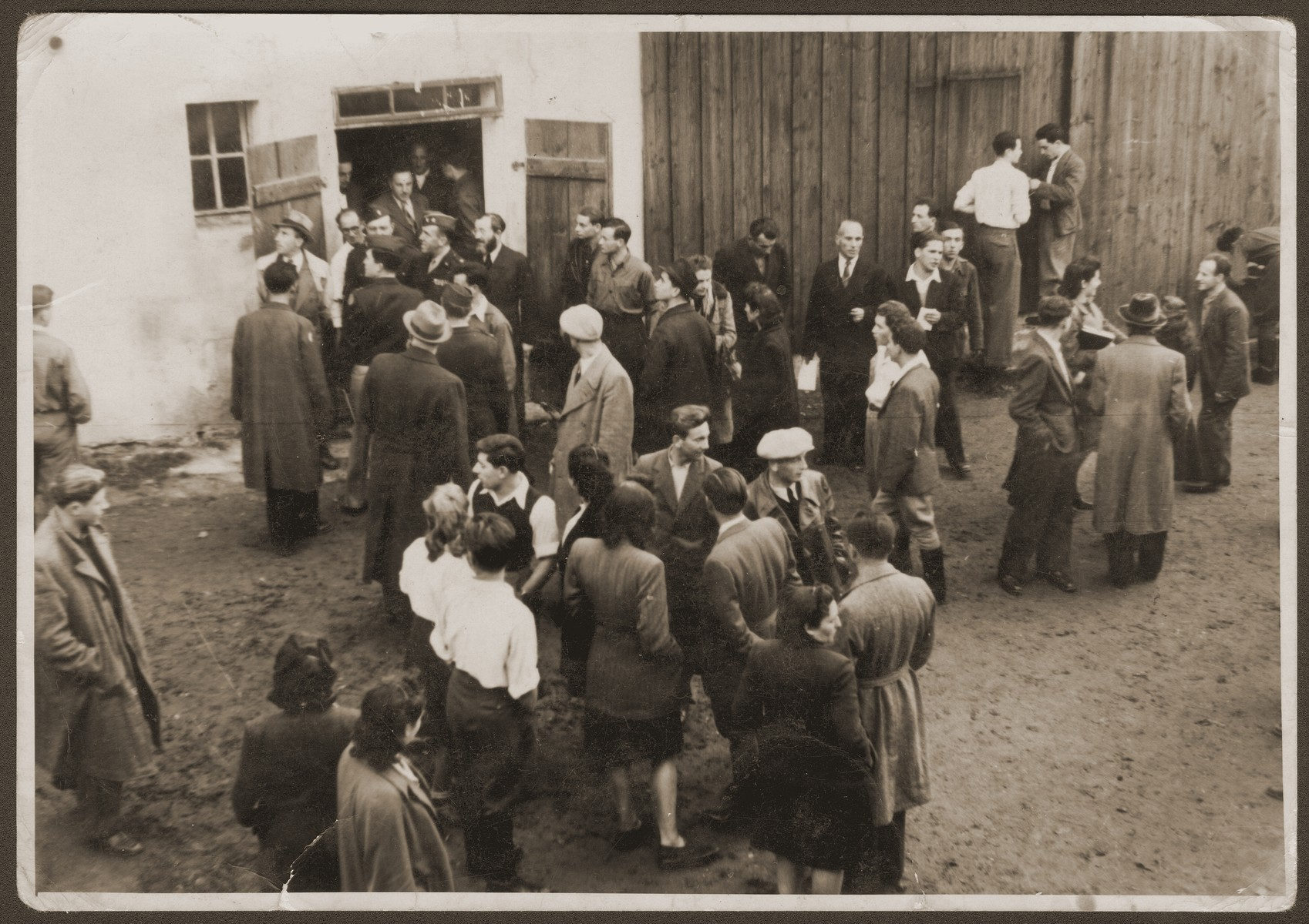 Official opening of the Zettlitz hachshara near Weiden, Germany.  US Army chaplain Saul Shapiro officiates at the opening.   Welek Luksenburg is pictured at the far left.  Hadasa Cudzynowski and Hinda Chilewicz are pictured in the foreground at the left with their backs to the camera.