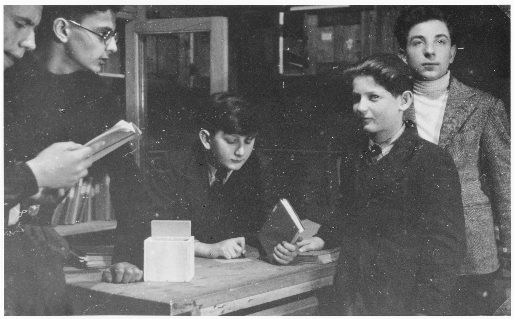 Ivar Segalowitz (center) and four other Jewish youths examine books in the library of the Champigny children's home.  Perry Shulman is on the far right.