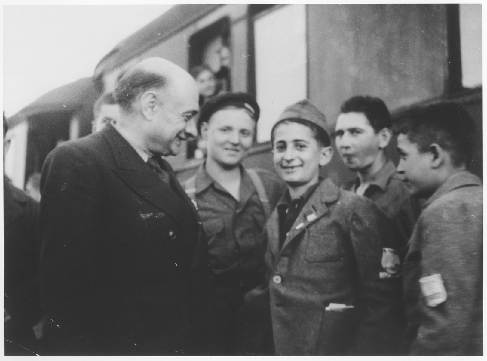 Lazare Gurvic greets members of the Buchenwald children's transport upon their arrival in the Les Andelys train station.  From here the children will be taken to the Ecouis children's home.