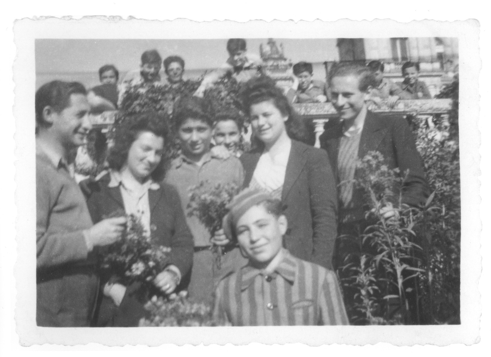 Members of the Buchenwald children's transport, one of whom is wearing a camp uniform, pose in the garden of the Ecouis children's home.  Among those pictured is Albert Dymant (far left); Jusek [Dishour] far right; Ivar Segalowitz (in the background, second from the left); and Léon Frydman (center between the two women, holding flowers).