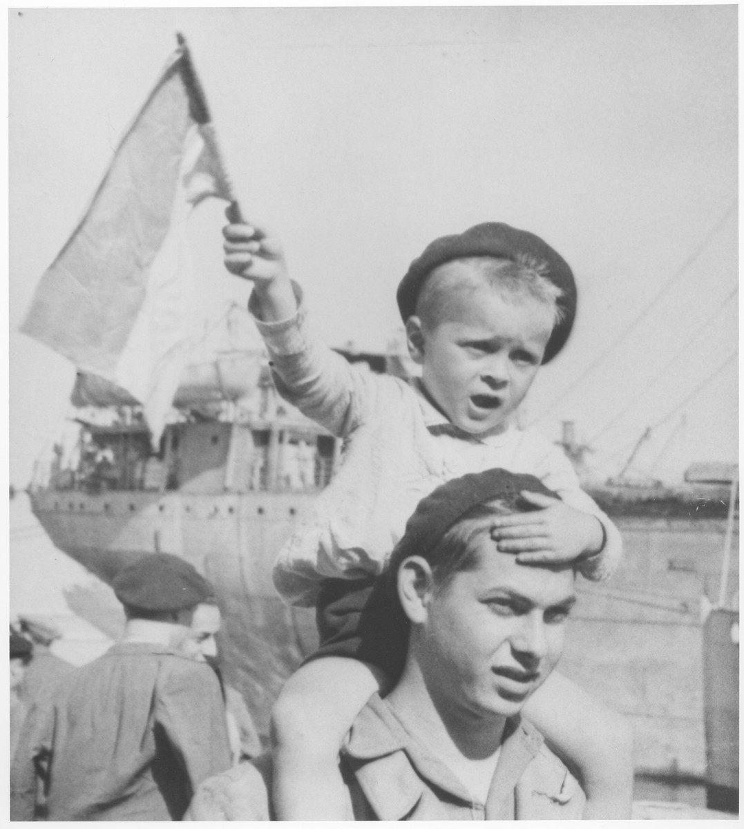 A young Jewish DP child waves a homemade flag while riding on the shoulders of an older boy at the port of Marseilles.    The two boys are about to board the RMS Mataroa for Palestine.