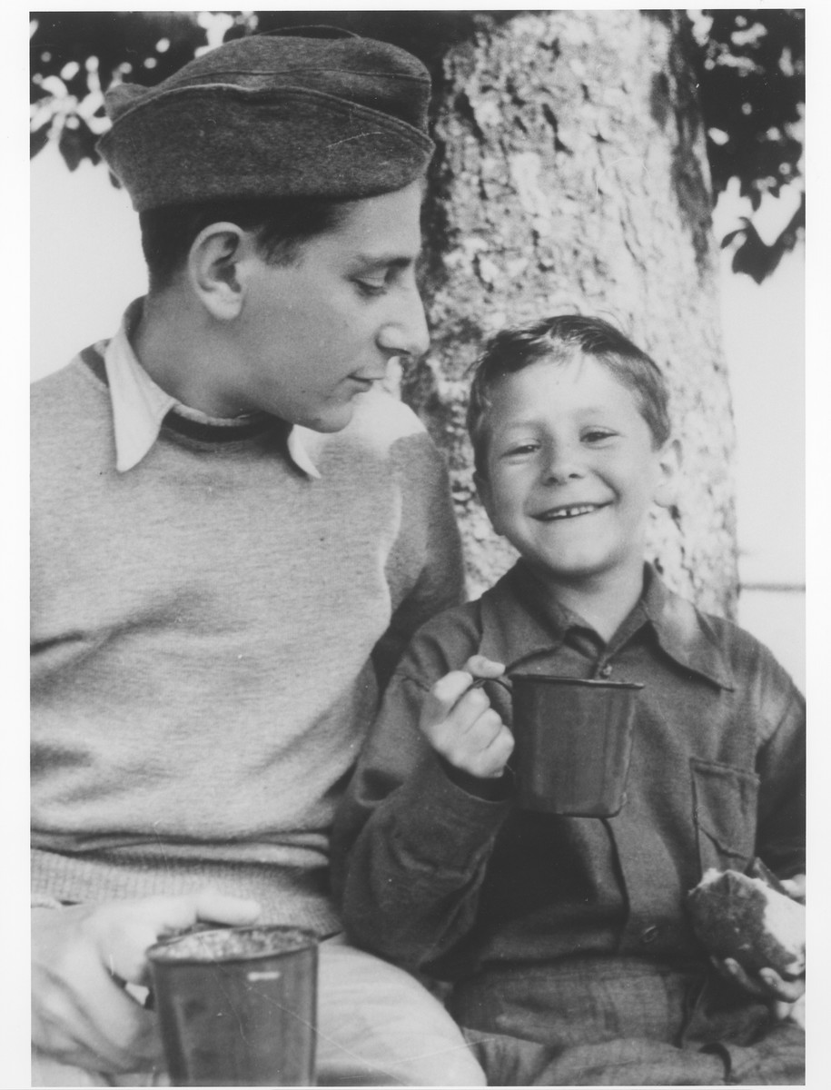 Two brothers who were members of the Buchenwald children's transport sit under a tree.  Pictured are Naftali (left) and Yisrael Meir (Lulek) Lau.