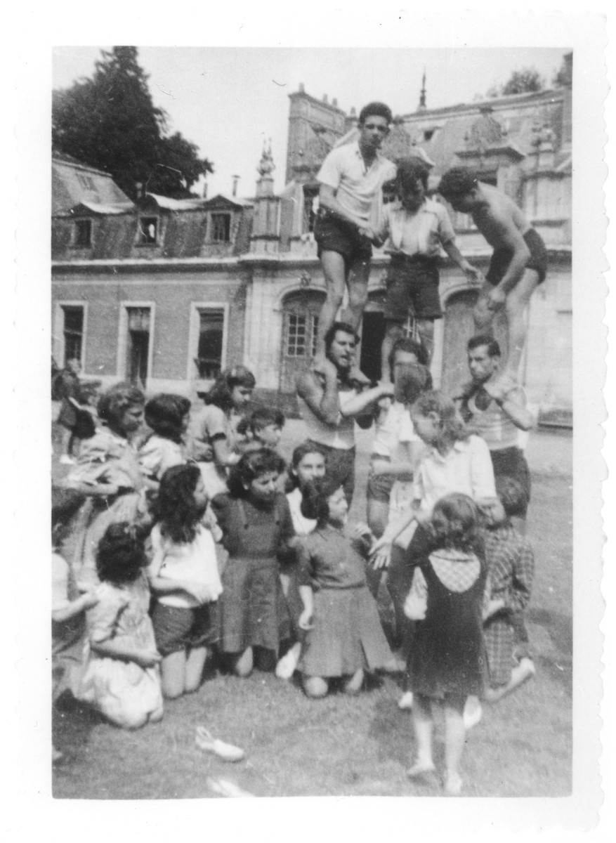 Jewish youth attempt to build a human pyramid in the yard of the Rothschild's Chateau Ferriere, where they are attending a summer camp sponsored by OSE.  Pictured at the very top of the pyramid is Ignacz Linzer.