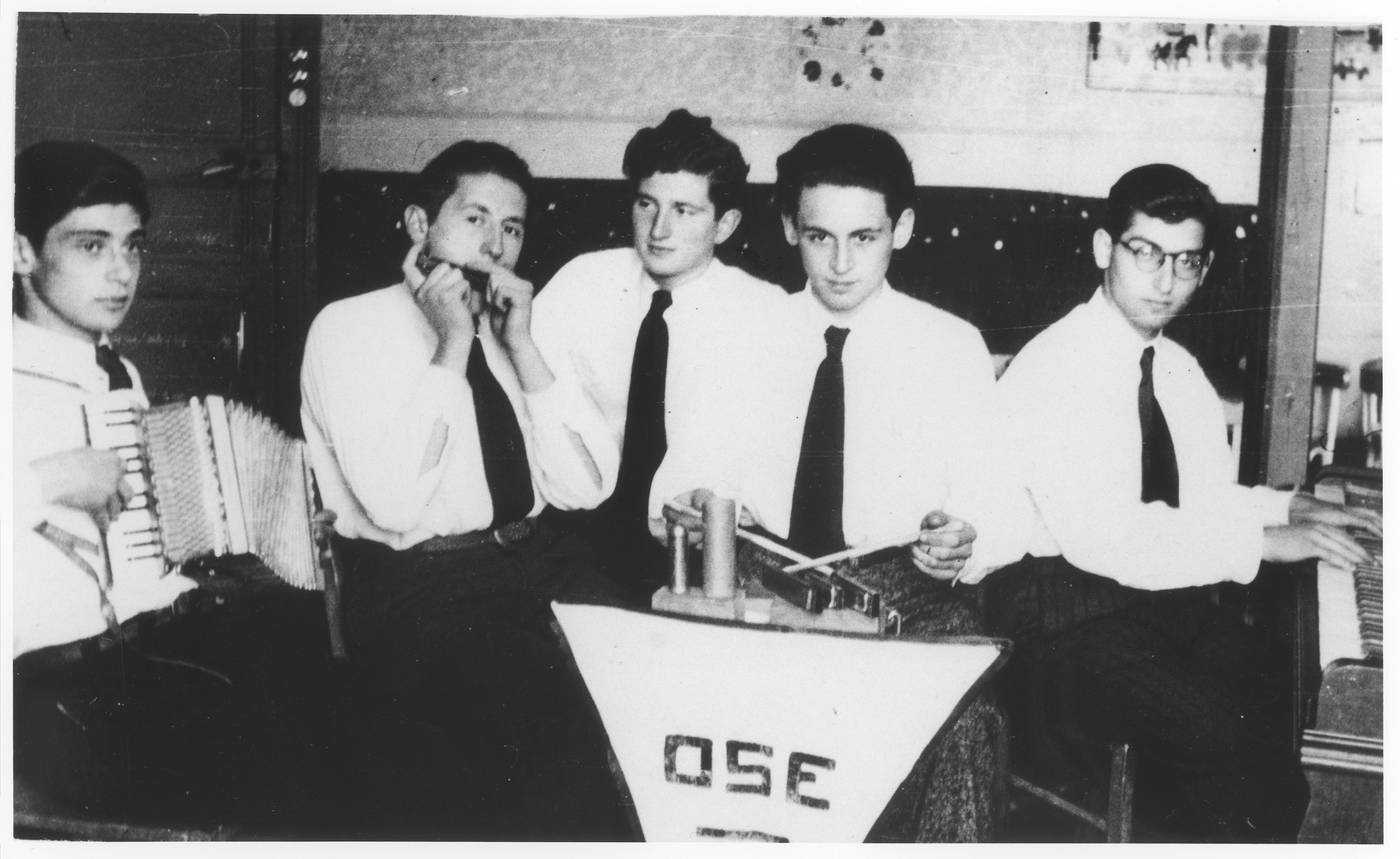 """Jewish refugee youth perform in a band at the Montintin children's home.  The orchestra called itself """"Orchestre Sans Espoir"""" [the orchestra without hope], a play on words for the initials OSE.  Pictured from left to right are Horst Rotholz, Werner Hausman, Guenther Heilbrun, Micki Stiasski and Hans Windmuller."""