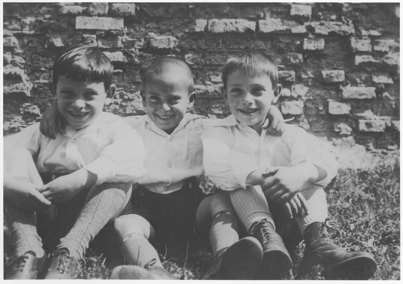 Three young Jewish boys pose in front of a brick wall.    Pictured from left to right are Fritz Neuberger, Werner Neuberger and their cousin, Max Mayer.