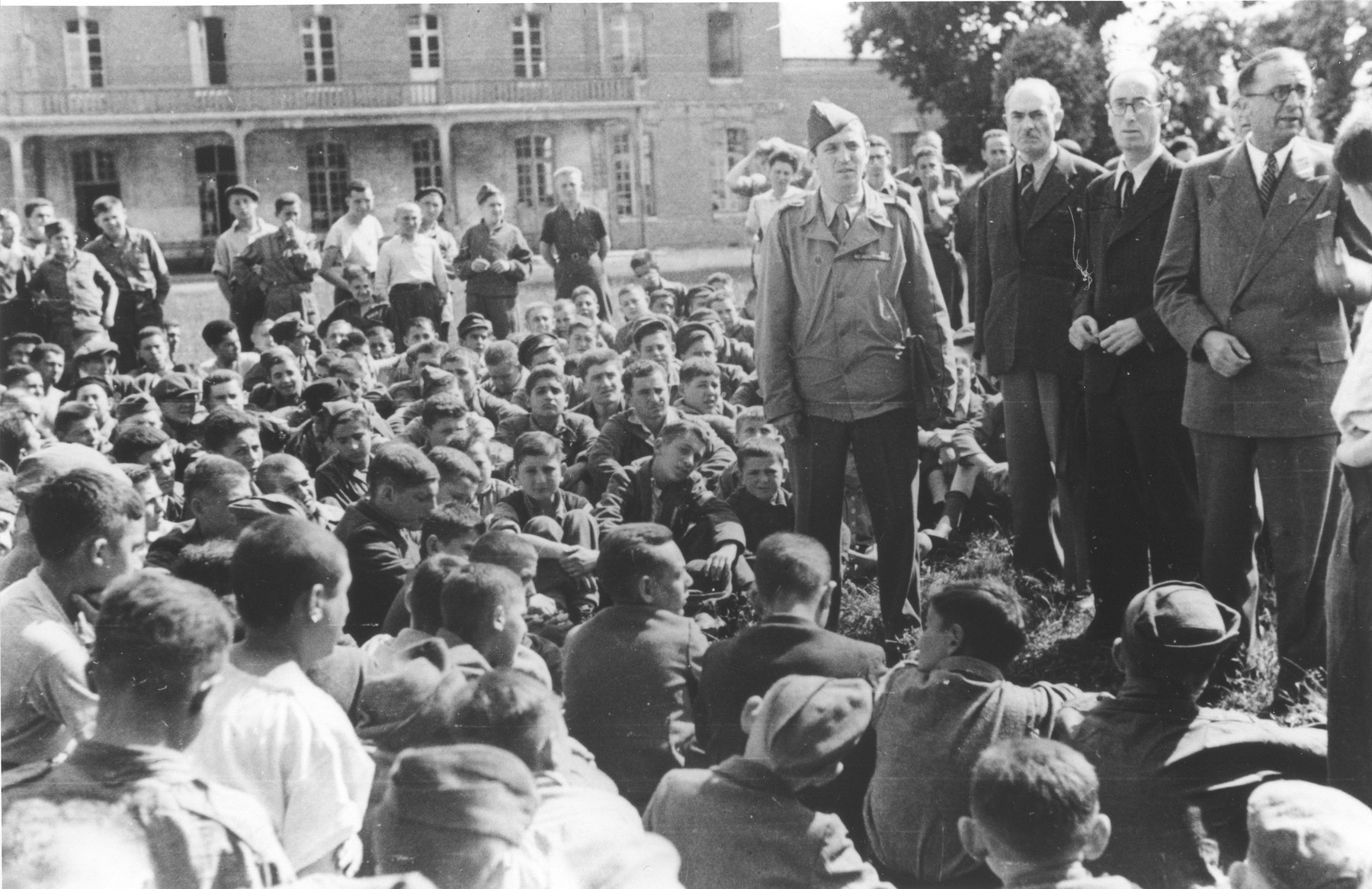 Jewish youth who were members of the Buchenwald children's transport listen to Colonel Rozen and representatives of the OSE at an outdoor meeting at the Ecouis children's home.