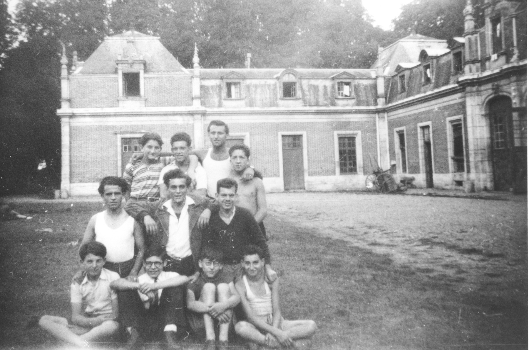A group of Jewish youth pose outside the Rothschild's Chateau Ferriere, where they are attending a summer camp sponsored by OSE.  Ivar Segalowitz is pictured standing in the back row at the far left.  Ignacz Linzer is standing next to him.