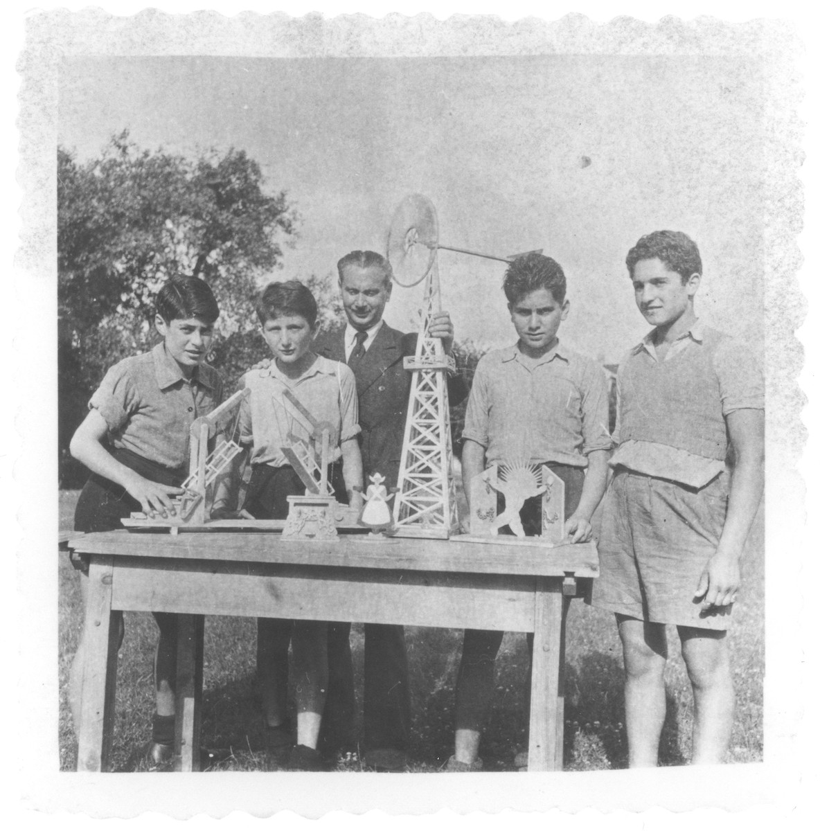 Ivar Segalowitz and three other boys display models that they made in a woodworking class in the Ecouis children's home.  Among those pictured are Hans Oster (left), Ivar Segalowitz (second from the left), and Janusz Podlaski (second from the right).