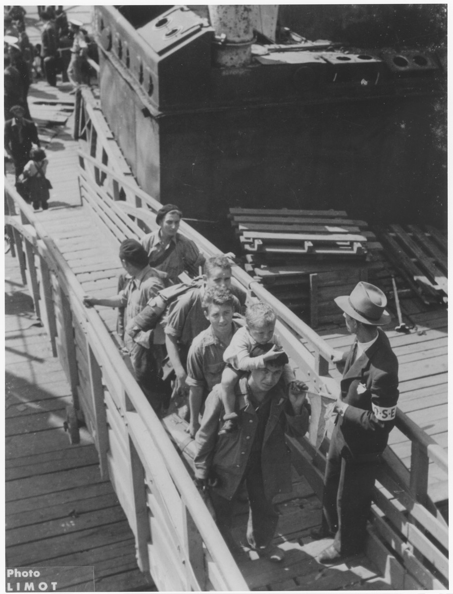 An OSE official supervises the boarding of the Buchenwald orphans onto the RMS Mataroa in the port of Marseilles.  At the head of the line, Yisrael Meir (Lukek) Lau is carried on the shoulders of his older brother Naftali.