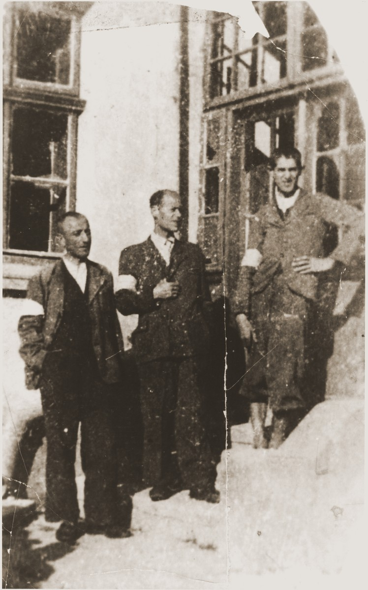 Three brothers wearing armbands pose on the stairs outside the carpentry workshop in the Berezhany ghetto.   Pictured are Oskar, Herman and Theodor Perl, the brothers of the donor, Rose Perl.