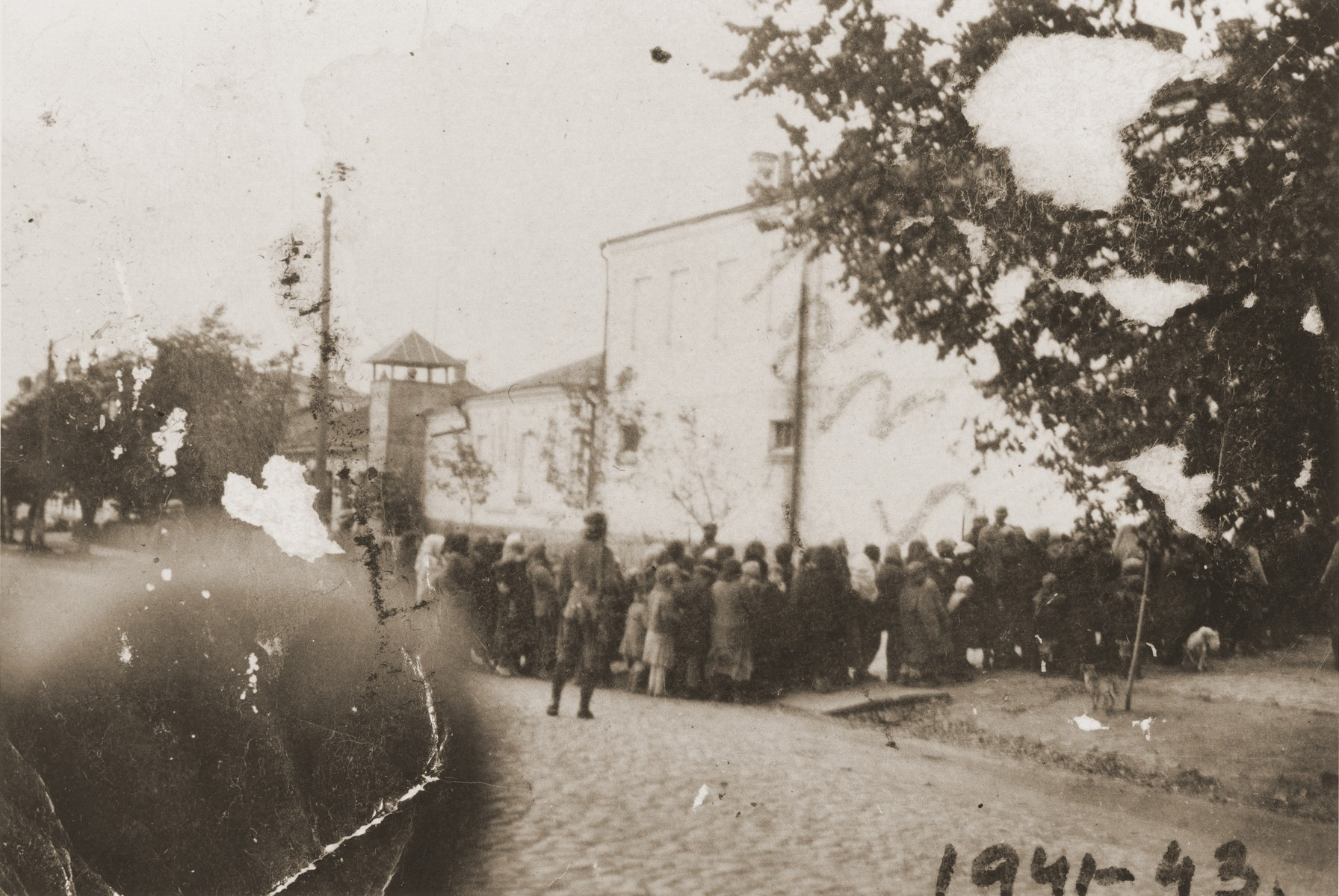 German guards oversee the assembly of Jews in Kamenets-Podolsk prior to their transportation to a site outside of the city for execution.