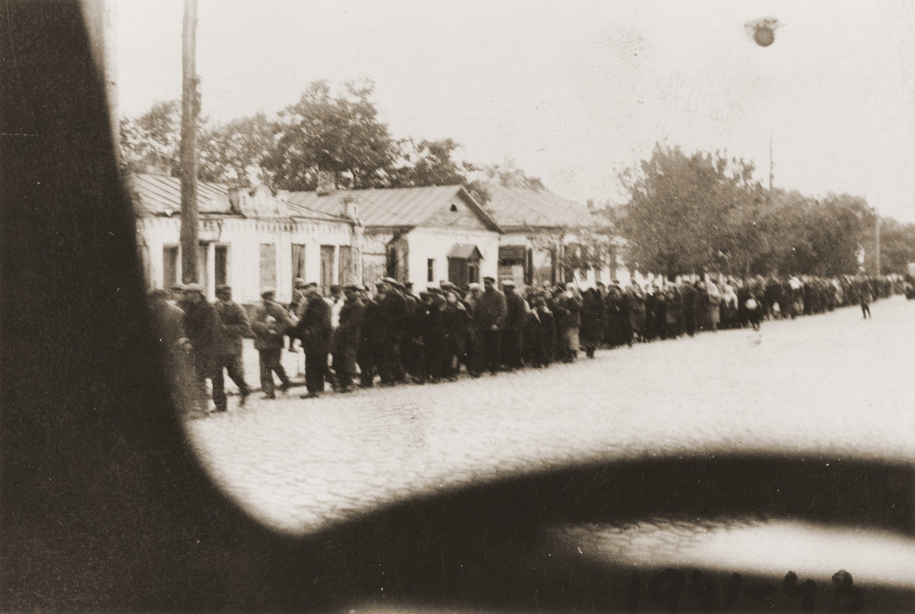 Jewish deportees under German guard march through the streets of Kamenets-Podolsk to an execution site outside of the city.