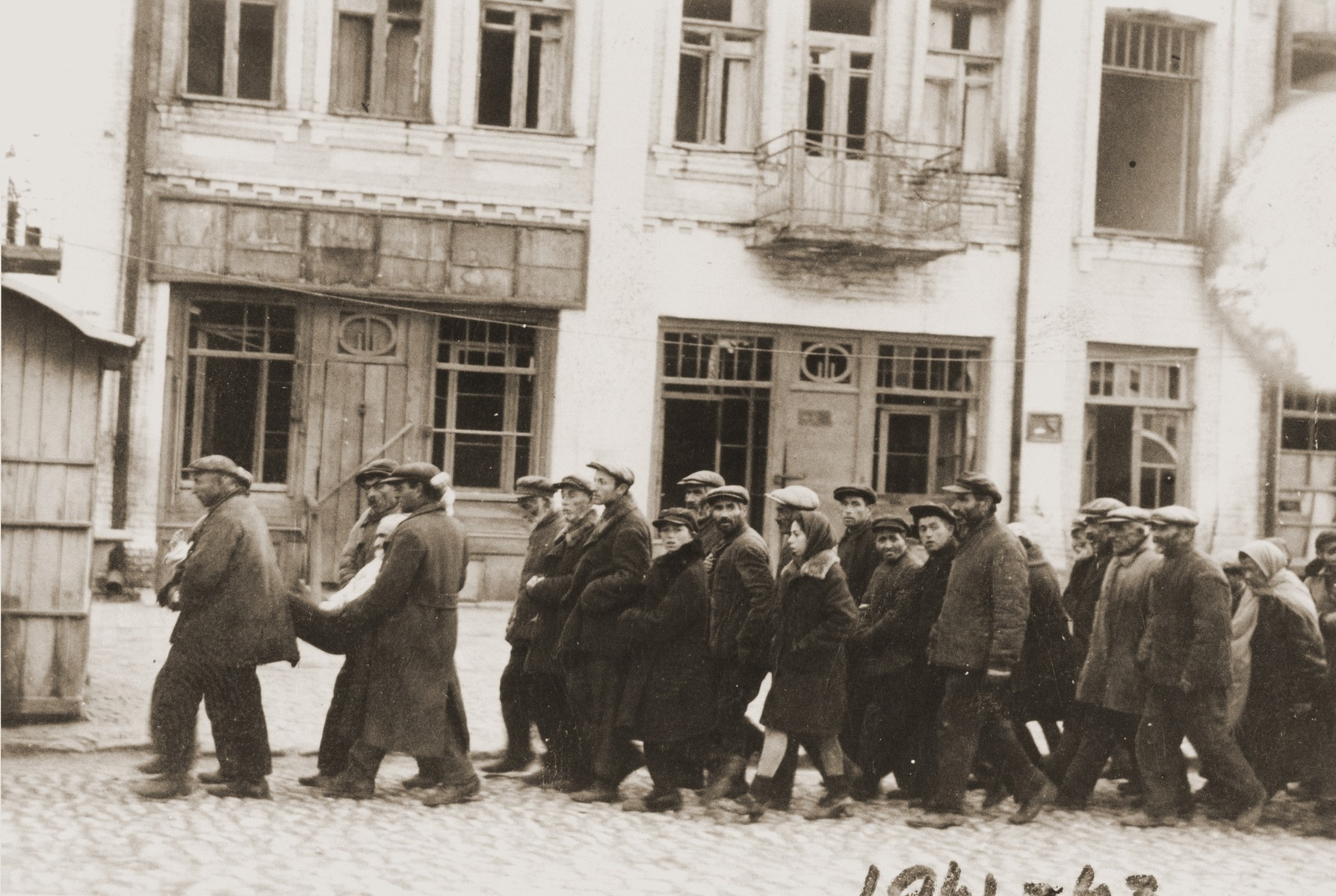 Jewish deportees march through the streets of Kamenets-Podolsk to an execution site outside of the city.