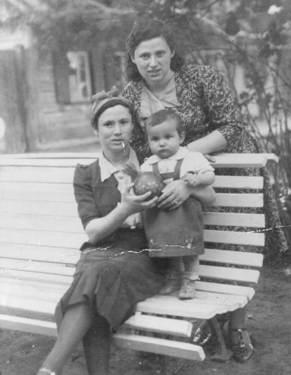 Two Jewish refugee women pose with a child on a park bench in Kaidan, Lithuania.  Pictured are Zlota (Levenstein) Ginsburg with her sister, Yocheved, and Zlota's youngest child.