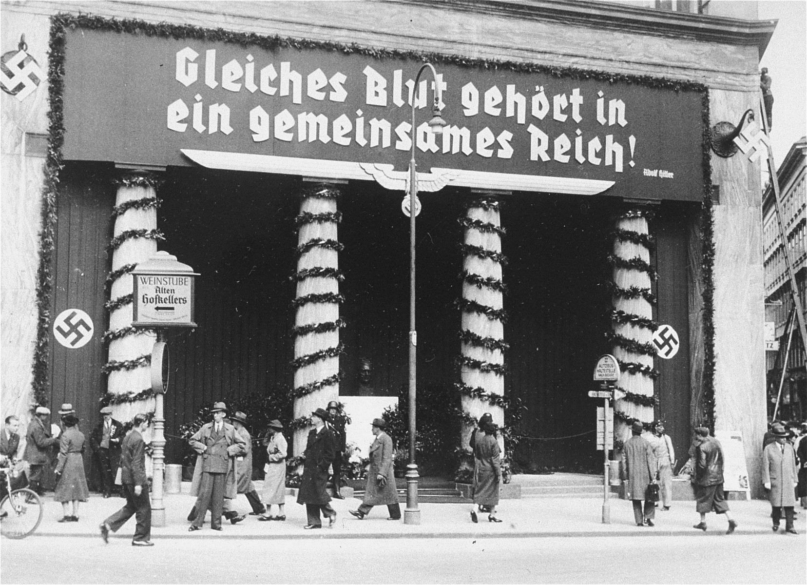 "View of the Loos Haus, a public building in Vienna, adorned with decorations and a large banner bearing a quote from Hitler, ""Those of the same blood belong in the same Reich!""    Such banners were hung throughout Austria in the weeks preceding the April 10th plebescite on the incorporation of Austria into the German Reich."