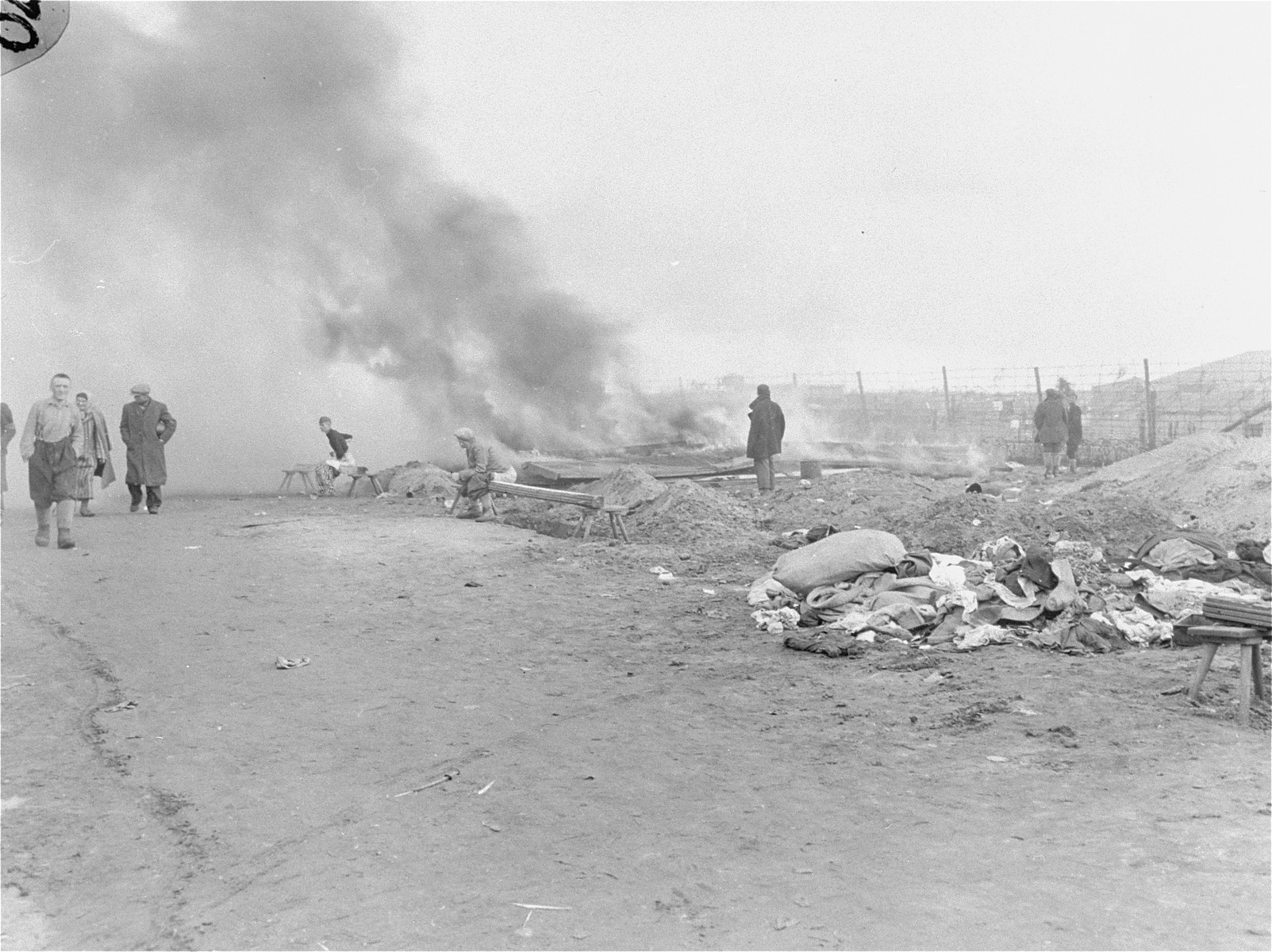 Billows of smoke rise up to the sky from typhus-infested barracks in Bergen-Belsen that have been torched by the British military.  A group of survivors move about just in front of the smoke.