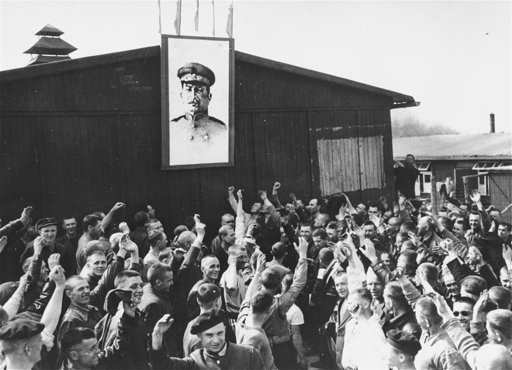 Survivors in Buchenwald cheer in front of a portrait of Stalin upon the liberation of the camp.