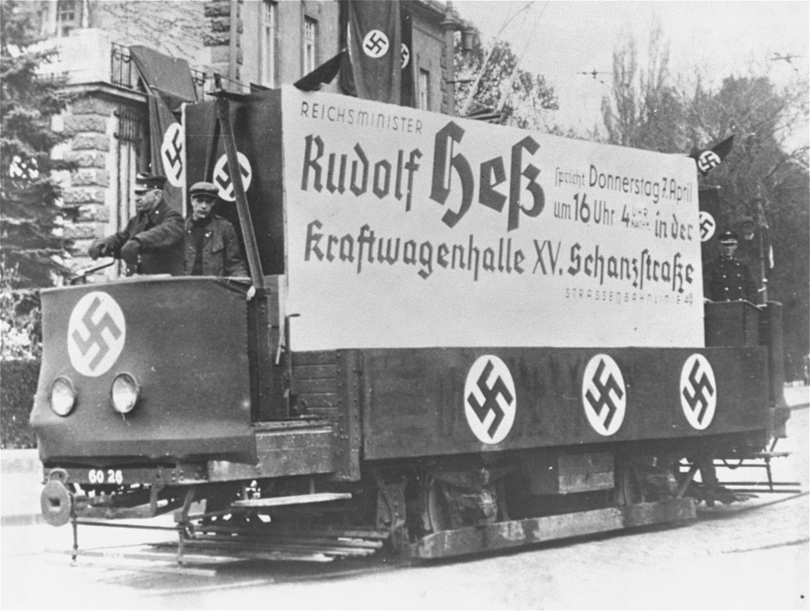 A streetcar adorned with swastikas and a large sign advertising a speech to be delivered by Reichsminister Rudoph Hess on April 7, 1938, in support of the Anschluss.
