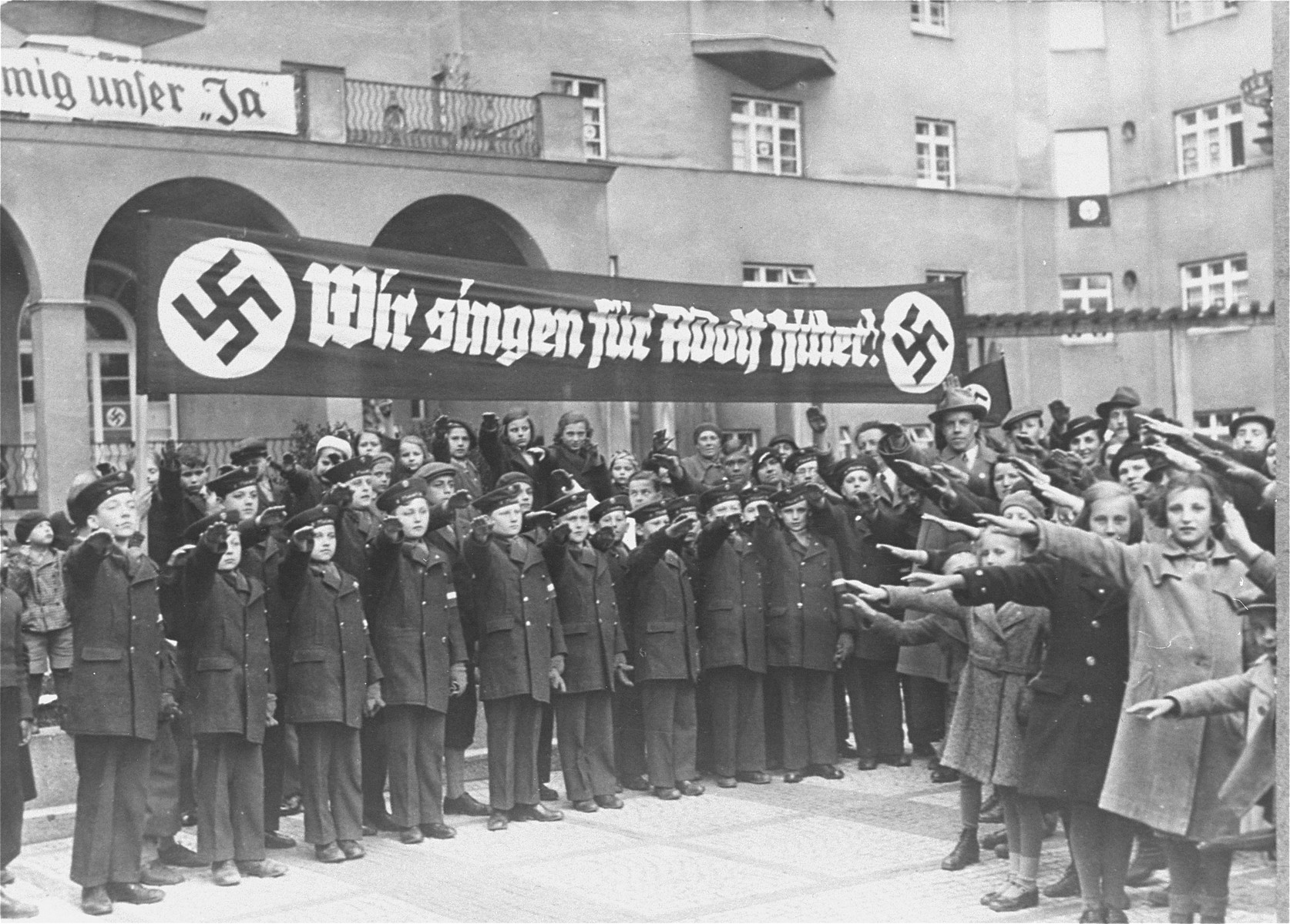 """The Vienna Boys' Choir, assembled under a banner that reads, """"We sing for Adolf Hitler!"""" salute Adolf Hitler and his entourage during his first official visit to Vienna after the Anschluss."""