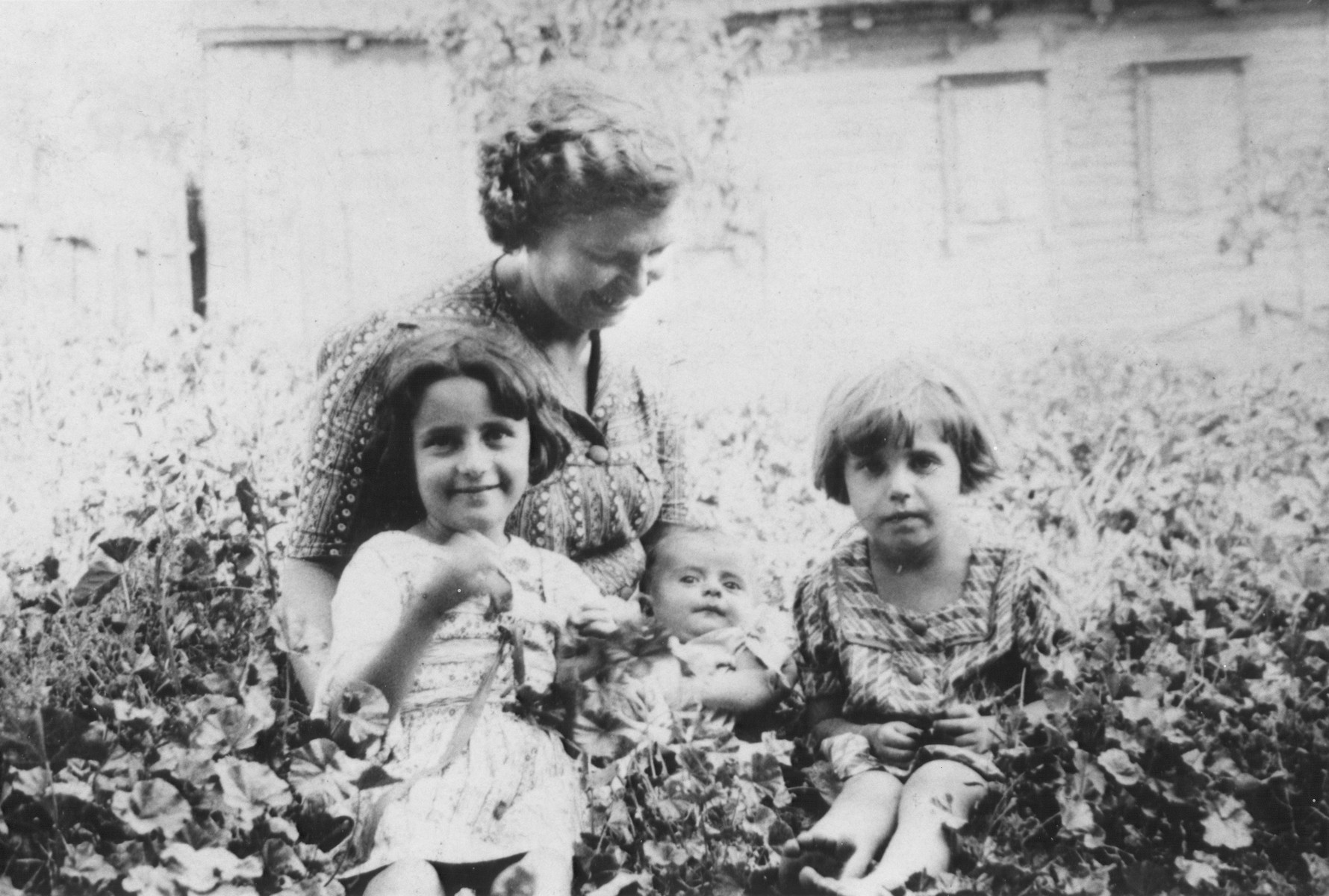A Jewish mother poses with her three daughters in Stolin, Poland.  All perished during the war.  The children pictured from left to right are Matle, Neche, and Esther Portnoy.