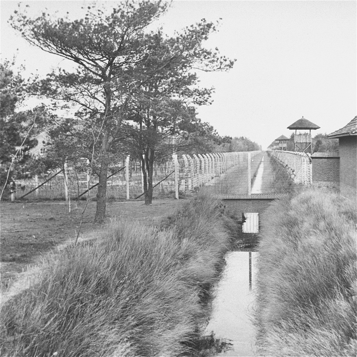 View of a section of the barbed-wire fence, moat and line of guard towers that surround the Vught transit camp.