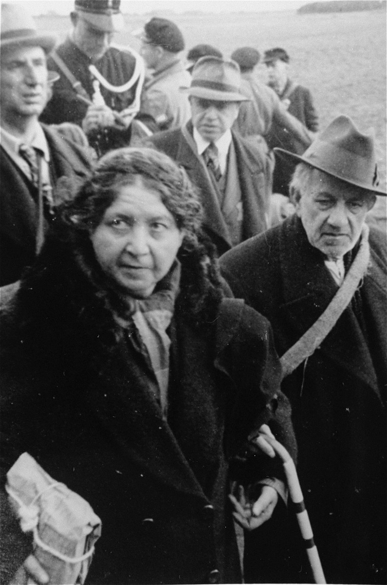 An elderly Jewish couple on their way from Hooghalen to the Westerbork transit camp.  A member of the Dutch constabulary stands behind them.  [oversized print]