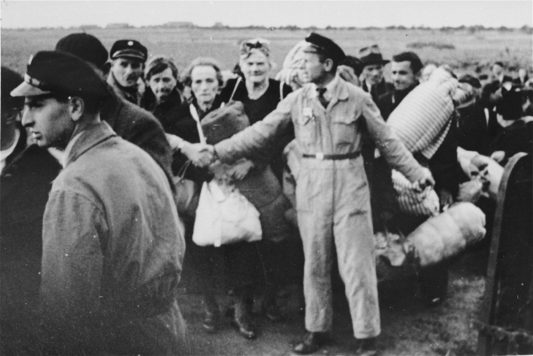 Members of the Ordedienst, the Jewish Police in Westerbork, direct an arriving transport of Dutch Jews into the camp.  The policeman in the center is A. Schoenfliess.