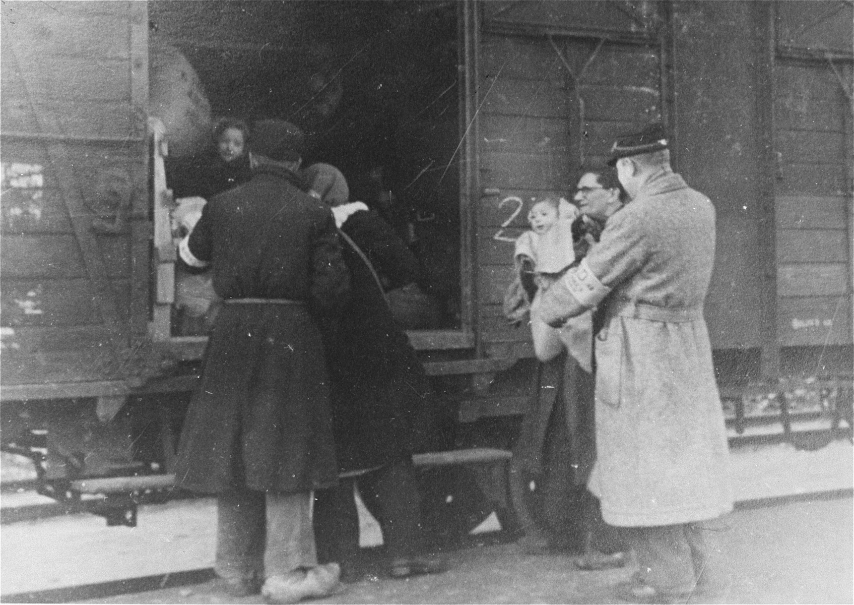 Members of the Ordedienst (Jewish police) give assistance to prisoners boarding a deportation train in the Westerbork transit camp.