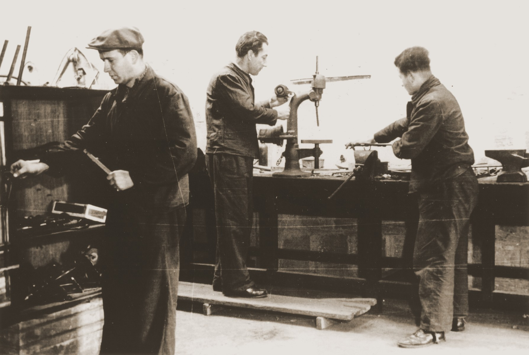 Jewish refugees at work in a metalshop in the Pingliang Road Home in Shanghai.  Pictured at the left is Viktor Stummer.