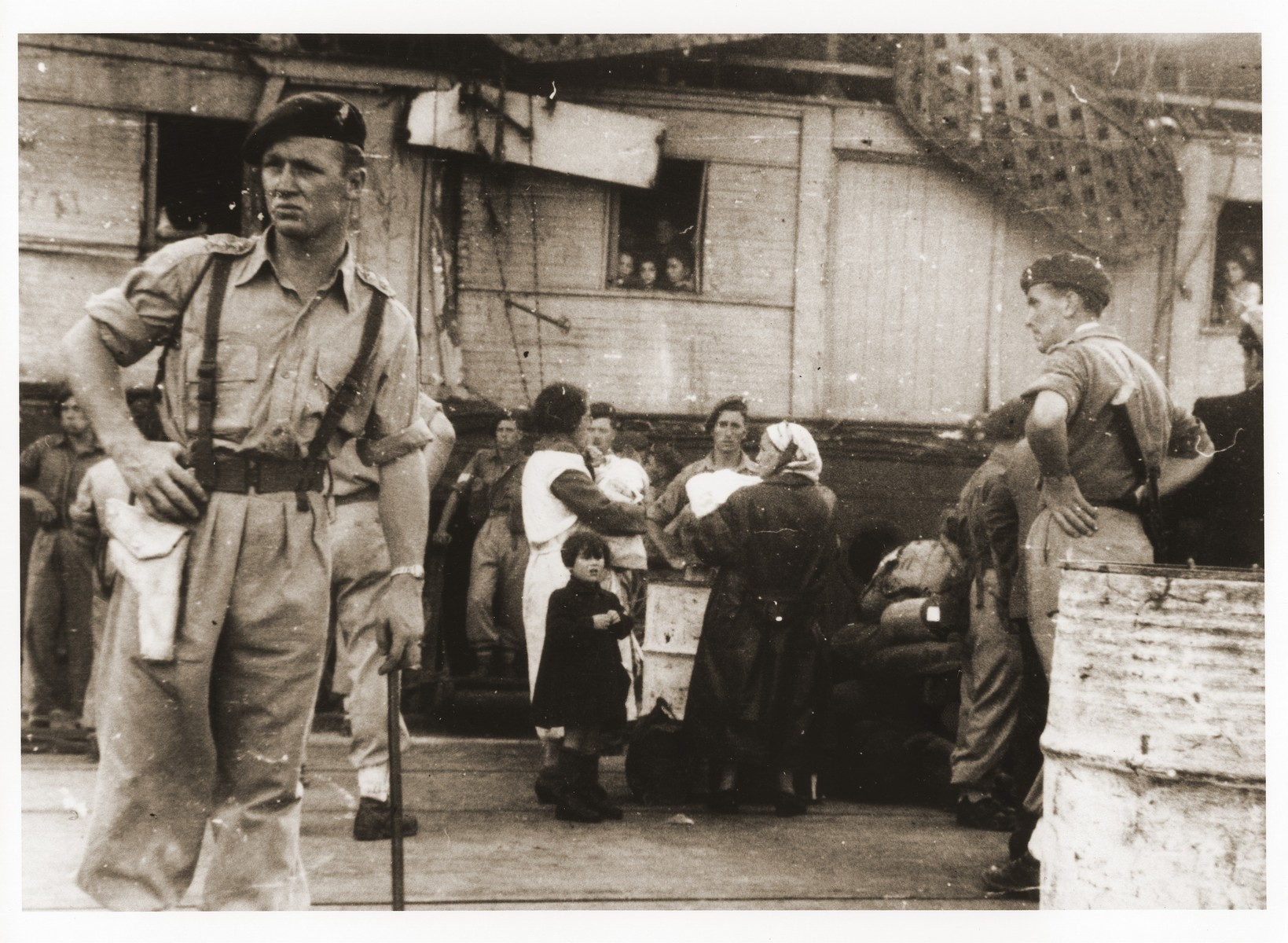 British soldiers stand guard on the pier in the port of Haifa as the passengers of the Exodus 1947 begin to disembark from the damaged ship.  The woman at the center left, wearing the white apron, holds her grandchild who was born on board the Exodus.  The child's mother died in childbirth.
