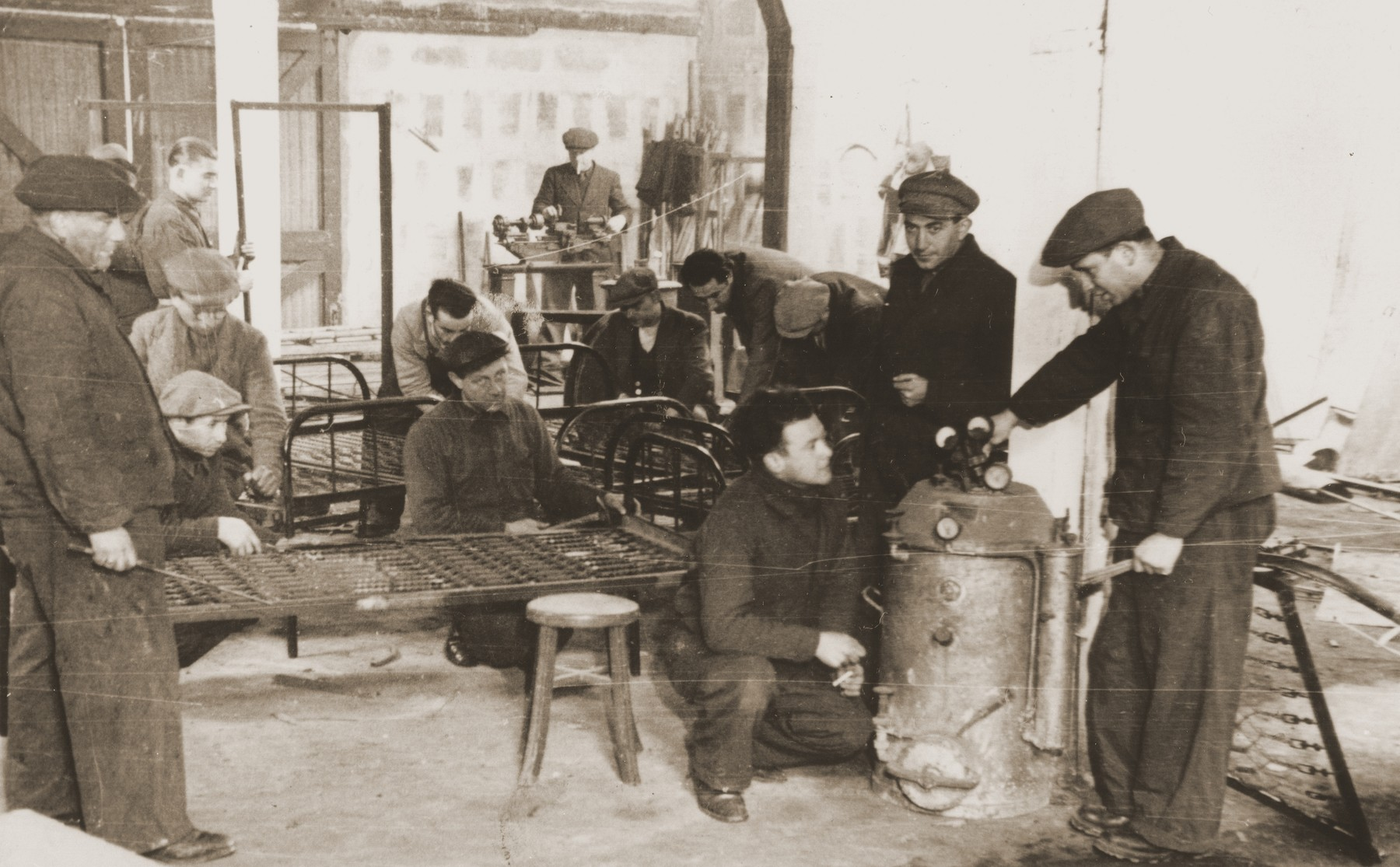 Jewish refugees assemble bedframes in a metalshop at the Pingliang Road Home in Shanghai.  Pictured at the far right is Viktor Stummer.