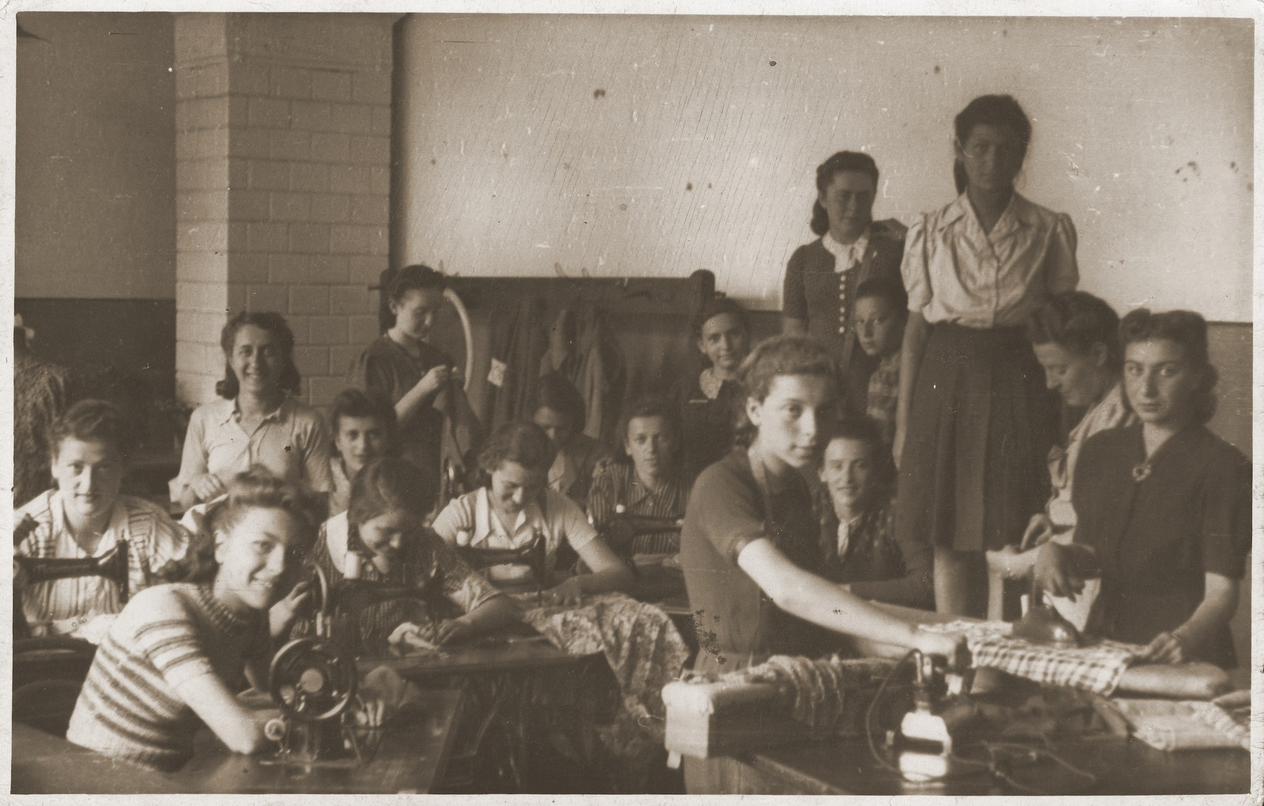 Sewing workshop in the Sosnowiec ghetto.    Seated in the middle is Hinda Chilewicz.  Standing from the right is Dorka Piorko, Fredka Landau and Cesia Chmielnicka.  Standing on the left is Mania Herszlikiewicz.