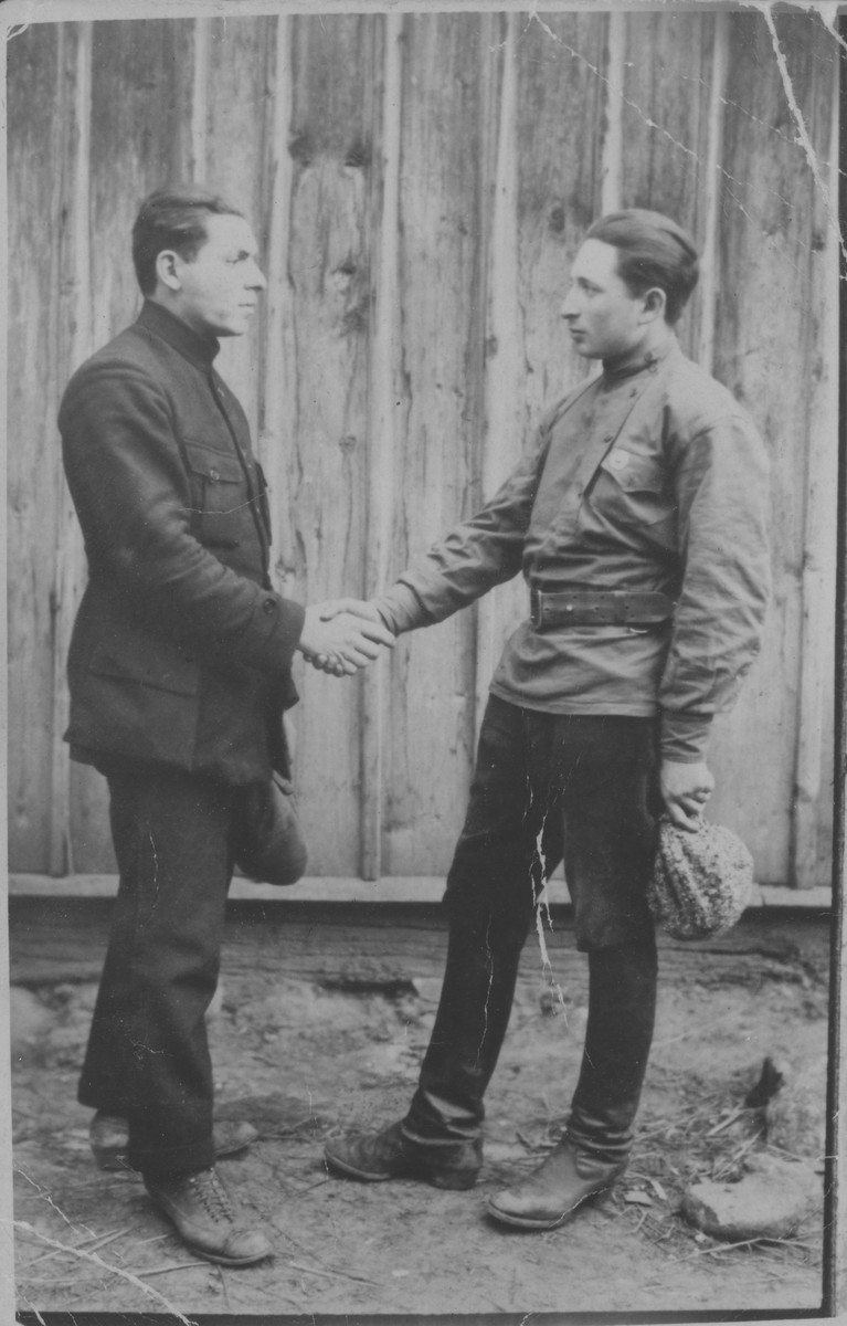 Two friends shake hands in front of a wooden wall.  Naftali Berkowitch is on the right and Israel Pogarelski on the left.  Naftali immigrated to Palestine.