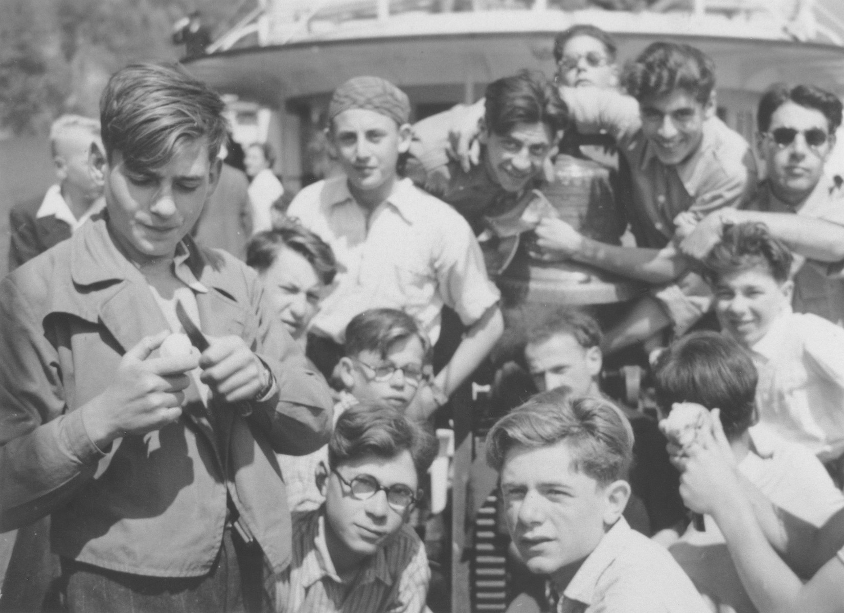 """Boys from the Hôme de la Forêt children's home on a summer boat excursion.  Among those pictured are Victor Grabsztok, Norbert Bikales, Simon Blass, Henri Karnowski, """"Bomba"""" Meyer and """"Jukoff"""".  Back row, second from the right  is Rudoph's brother."""