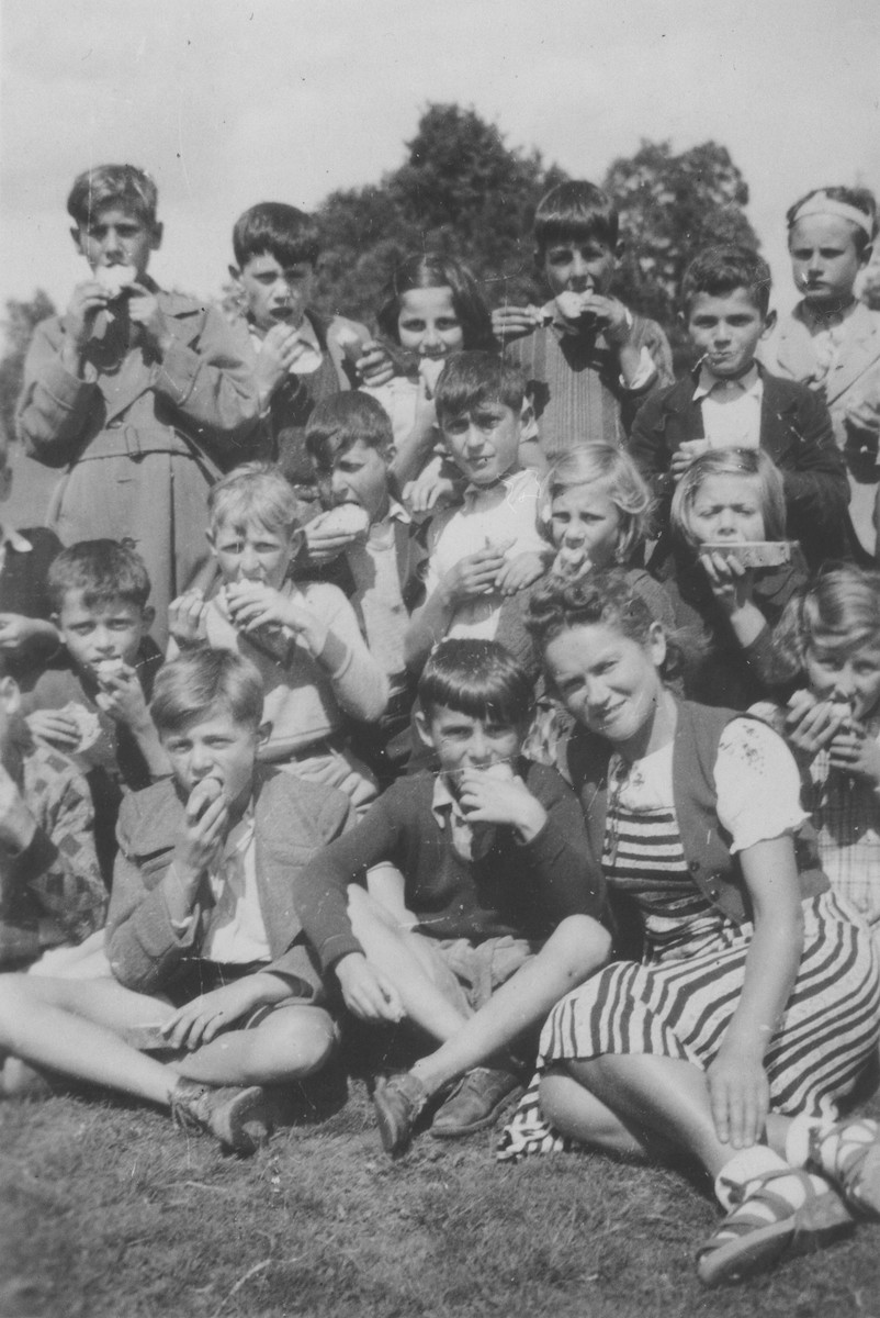 Jewish refugee children eat an afternoon snack outside at the Chabannes children's home.  Among those pictured are the teacher, Jitta Zylberstejn, and the children: Norbert Bikales, Gerhard Glass, Michel Razimowski, Ivan Rossman, Georges Jacob, Anatol Zylberstein and Arno Marcuse.
