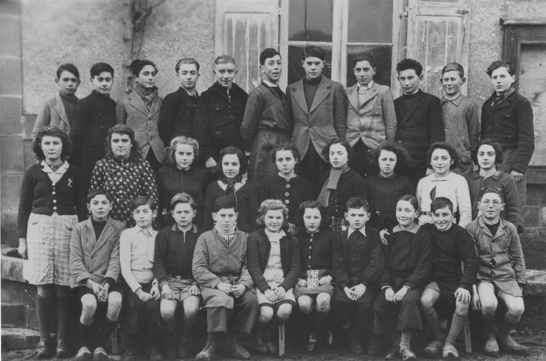 Class portrait of students at the Ecole Saint Pierre de Fursac, a school attended by Jewish refugee children living at the Chabannes children's home, as well as those from the village.   Pictured in the front row, from left to right are: unknown; Pierre Lafaye; Jo Jacob; unknown; Renaud; Andre Dubois; unknown; Margot Weinberg; Plavinet; Andre Lelong; Kostia Sotnikov.  Second row: Paulette Leblanc; Marcelle Fedon; unknown; Grosset; Irene Clement; Jeanne Luguet; Paulette Legris; Gisele Brunetaud; Ginette Chanliat.  Third row: Mamet; Georges Loeffler; Norbert Bikales; Michel Razymovsky; Madeleine Boramier; Madeleine Basset; Anatole Zylberstein; unknown; unknown; unknown.