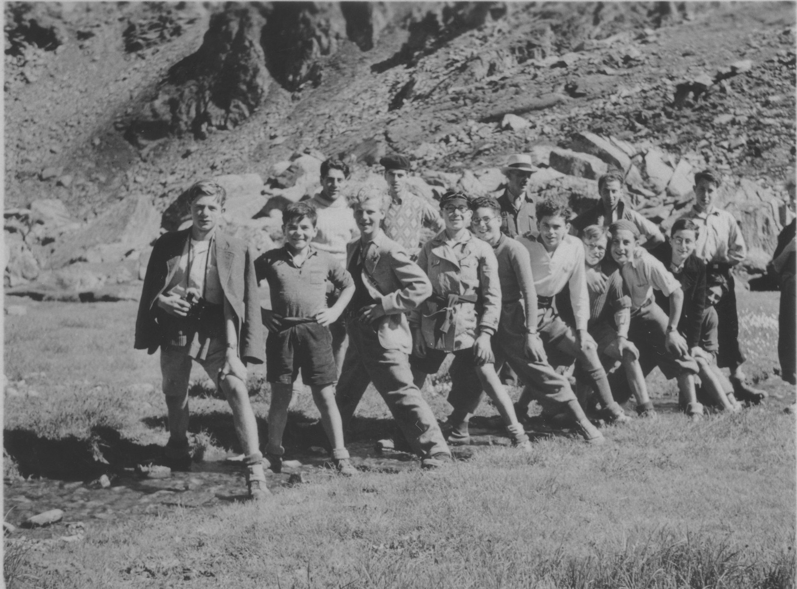 "Boys from the Hôme de la Forêt children's home pose by the source of the Rhine with one foot on either shore.  Those pictured include ""Jukoff"", Henri Karnowski, Victor Grabsztok, Norbert Bikales, Simon Blass, and Gilles Segal."