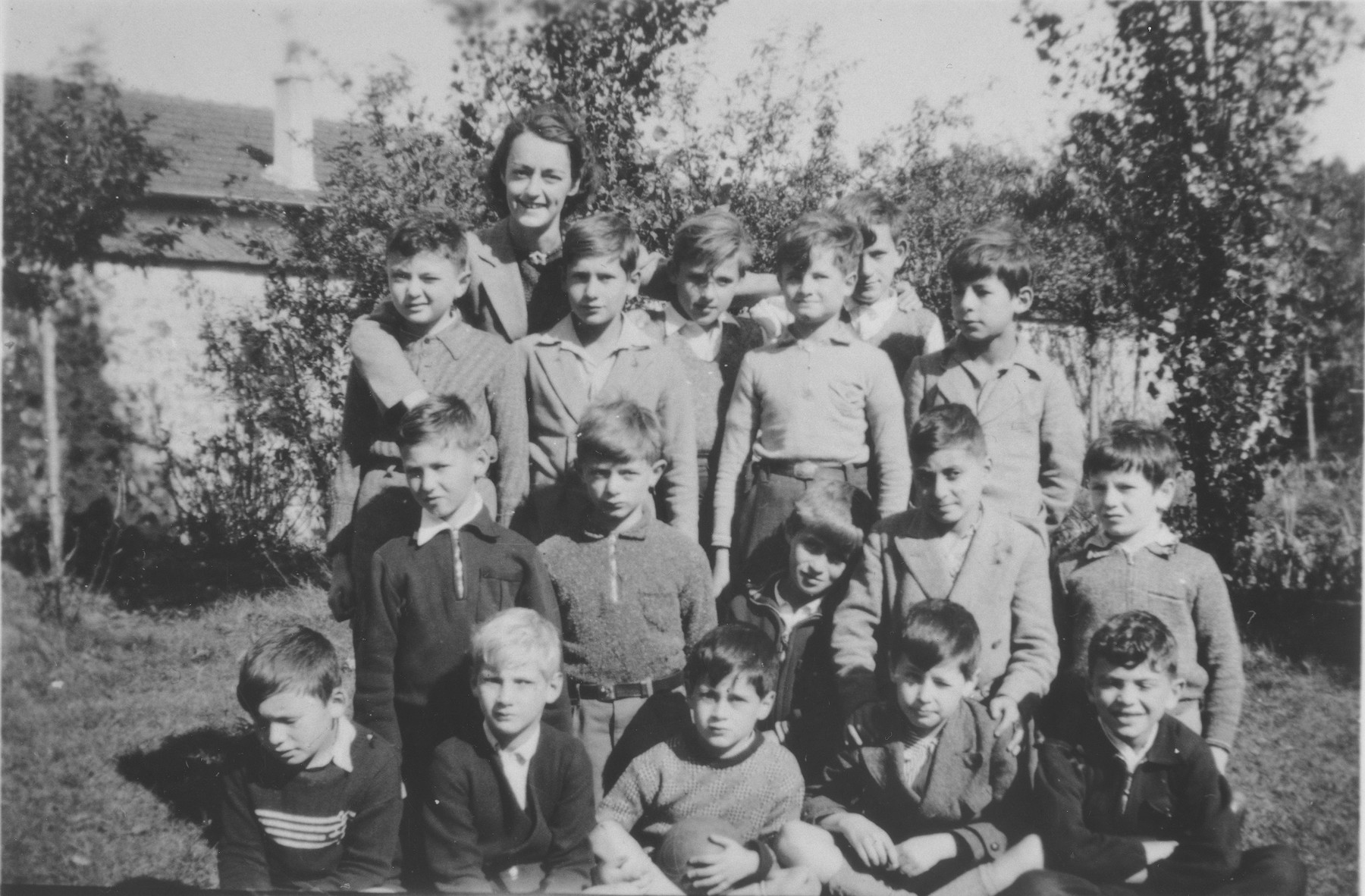 Raymonde Sauviac, a teacher at the Quincy children's home, poses with a group of Jewish refugee boys who arrived on a Kindertransport from Germany.  Sauviac was later recognized by Yad Vashem as one of the Righteous Among the Nations for her role in rescue efforts in France.  Pictured in the front row from left to right are:  Henry Hoppenstandt, Ralph Moratz, Werner Gossels, Peter Gossels and Wolodya Grajonza.  Second row: Karll Heinz  Wolfberg, Norbert Bikales, Sammy Stuck, Erwin Cosman and Herbert Oberniker.  Third row: Werner Goldschmidt, Gerhard Glass, Henri Kreft, Arno Marcuse, Egon Zwirn and Berthold Friedlander. Top: Mlle. Raymonde Sauviac (later Fanouillere).