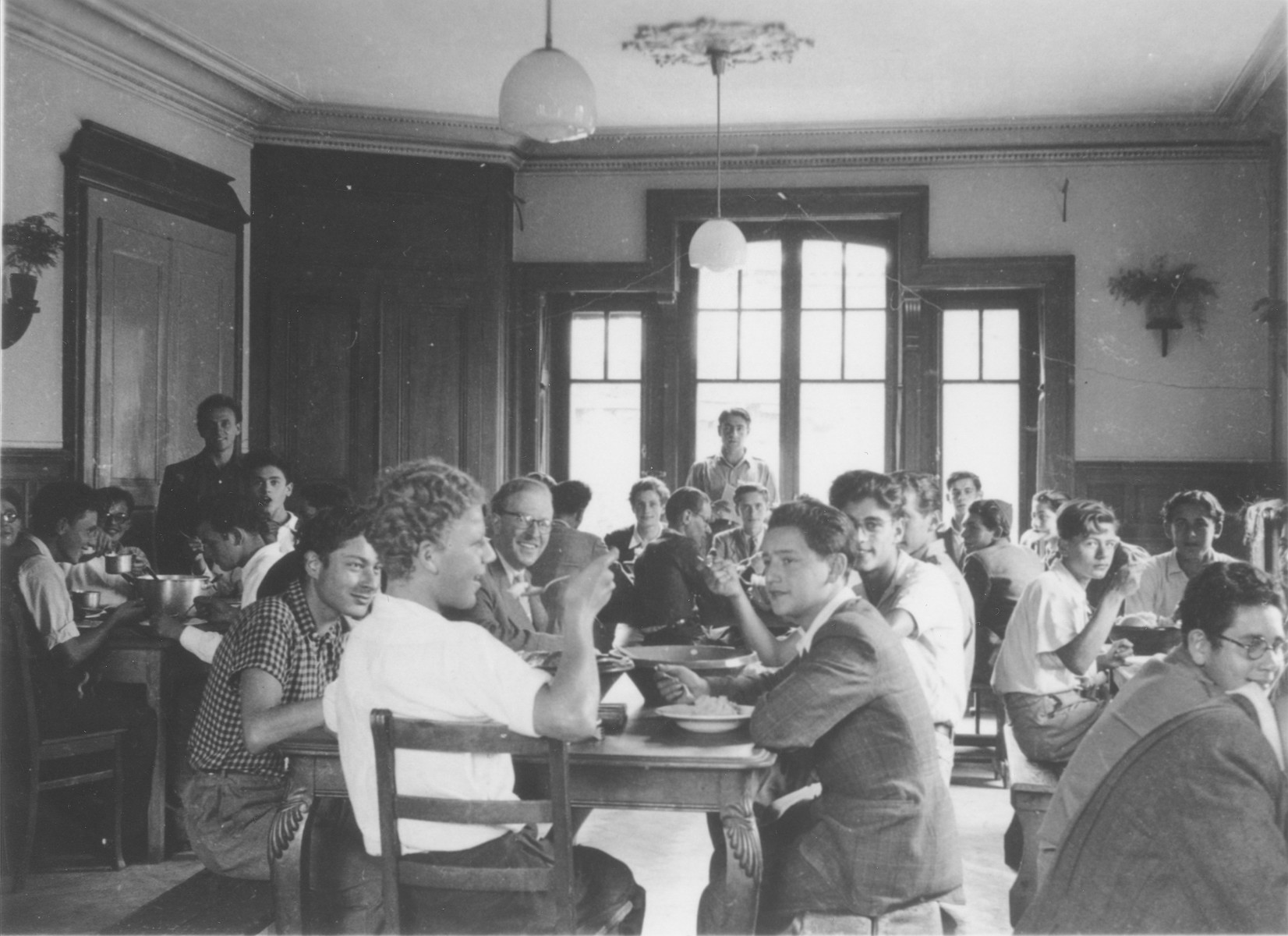 Residents of the Hôme de la Forêt children's home eat a meal in the dining hall.