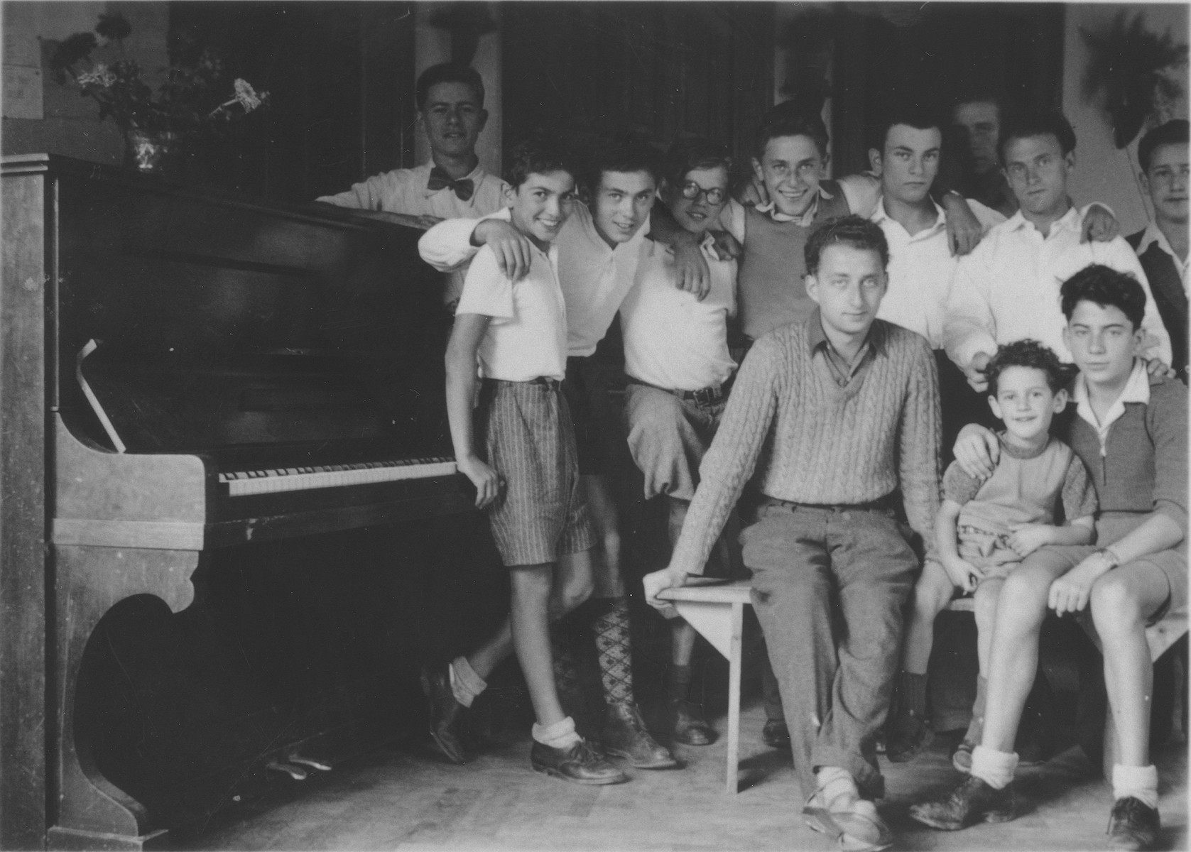 A group of boys gathers around a piano in the Hôme de la Forêt, a children's home run by the (Oeuvre de Secours aux Enfants) in Geneva, Switzerland.  Among those pictured are Gilles Segal, Norbert Bikales, Henri Karnowsky, Victor Karnowsky and Gert Silberbard (later Gert Silver) (center).   Leaning on the piano is Rudoph.