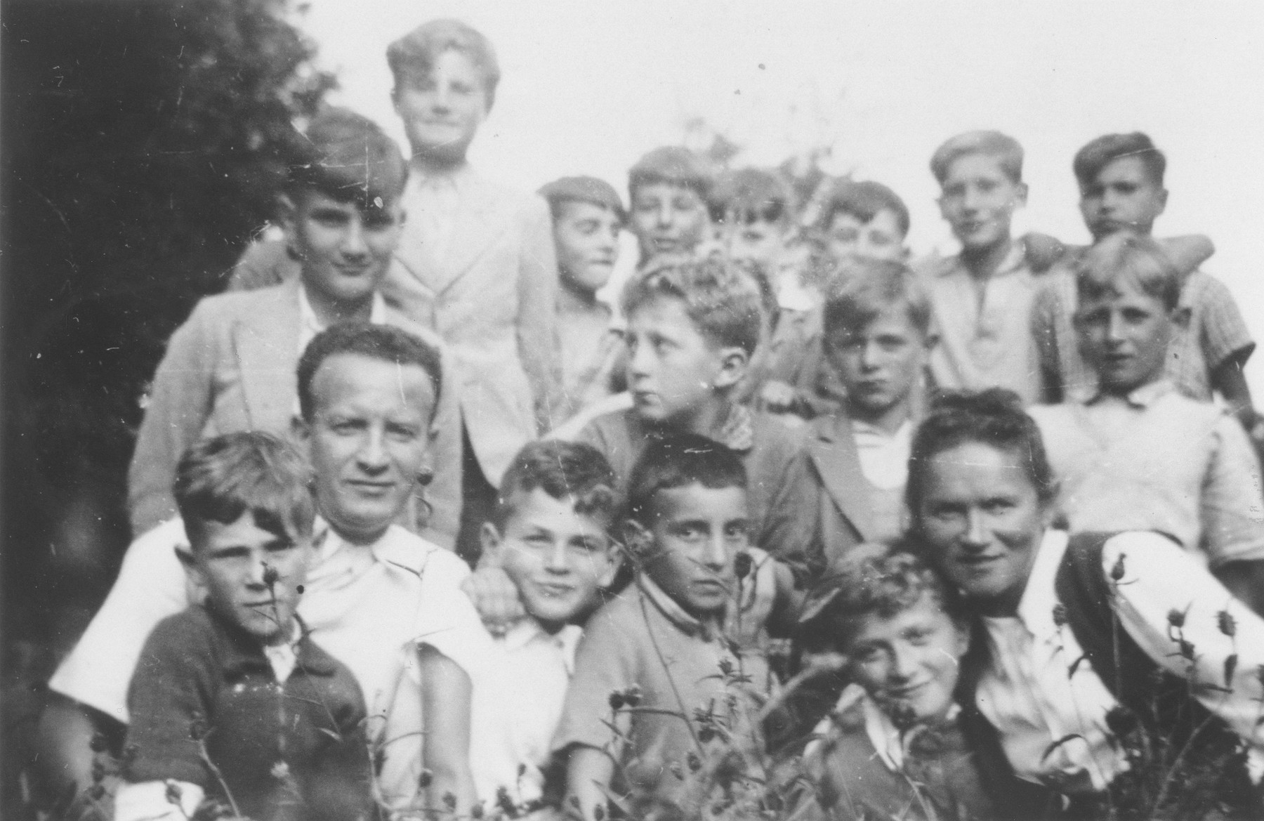 OSE teachers Mr. and Mrs. Zitta Zylberstein pose with a group of children outside the Chabannes children's home.  Also pictured are Albert Nadel, Anatole Zylberstein, Gunter Moser, David Nadel, Hans Stern, Kurt Fischof, Norbert Bikales, Michel Bronsztein, Arno Marcuse, Georges Wajnberg, Berthold Friedlaender, Herbert Abormitter, Klaus Gossels, Gerhard Glass, and Alfred Nowack.