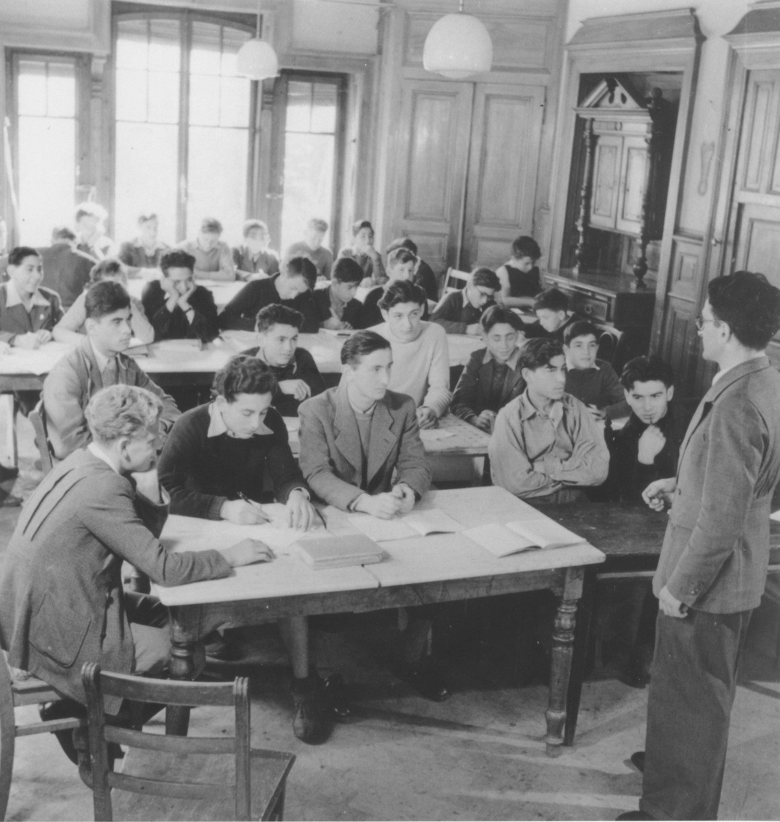 Isidor Bernstajn teaches a Yiddish class in Hôme de la Forêt children's home.  Among those pictured is Jacques Karpensztein (later Carpentier, b. May 29, 1929, d. December 23, 1989) in the second row, wearing a white sweater.