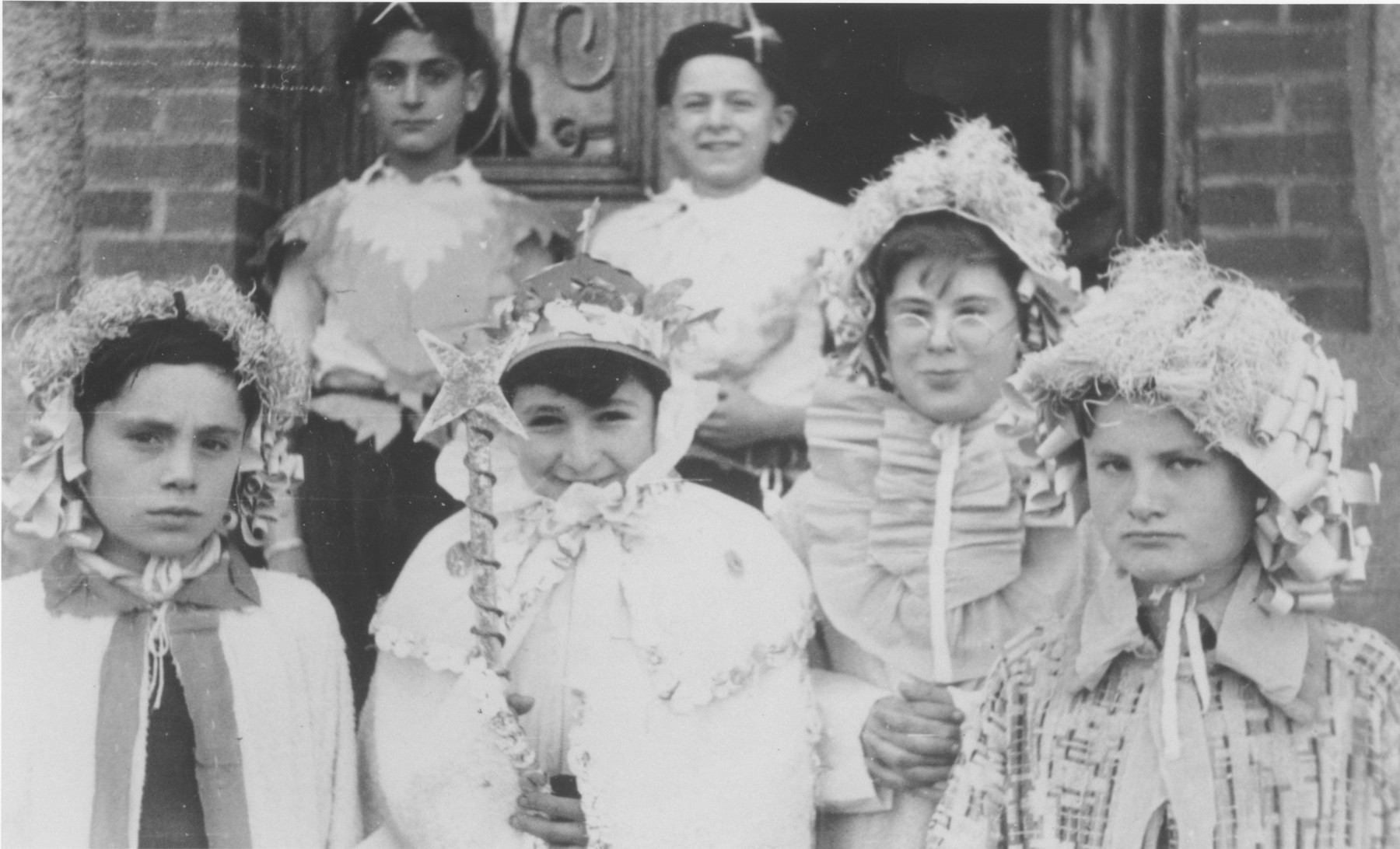 Jewish refugee children in the Chabannes children's home pose dressed in Purim costumes.  Pictured from left to right are Michel Razymovsky, Georges Sztrum and Arnaud Marcouse.  Standing are Georges Jacob and Norbert Bikales.