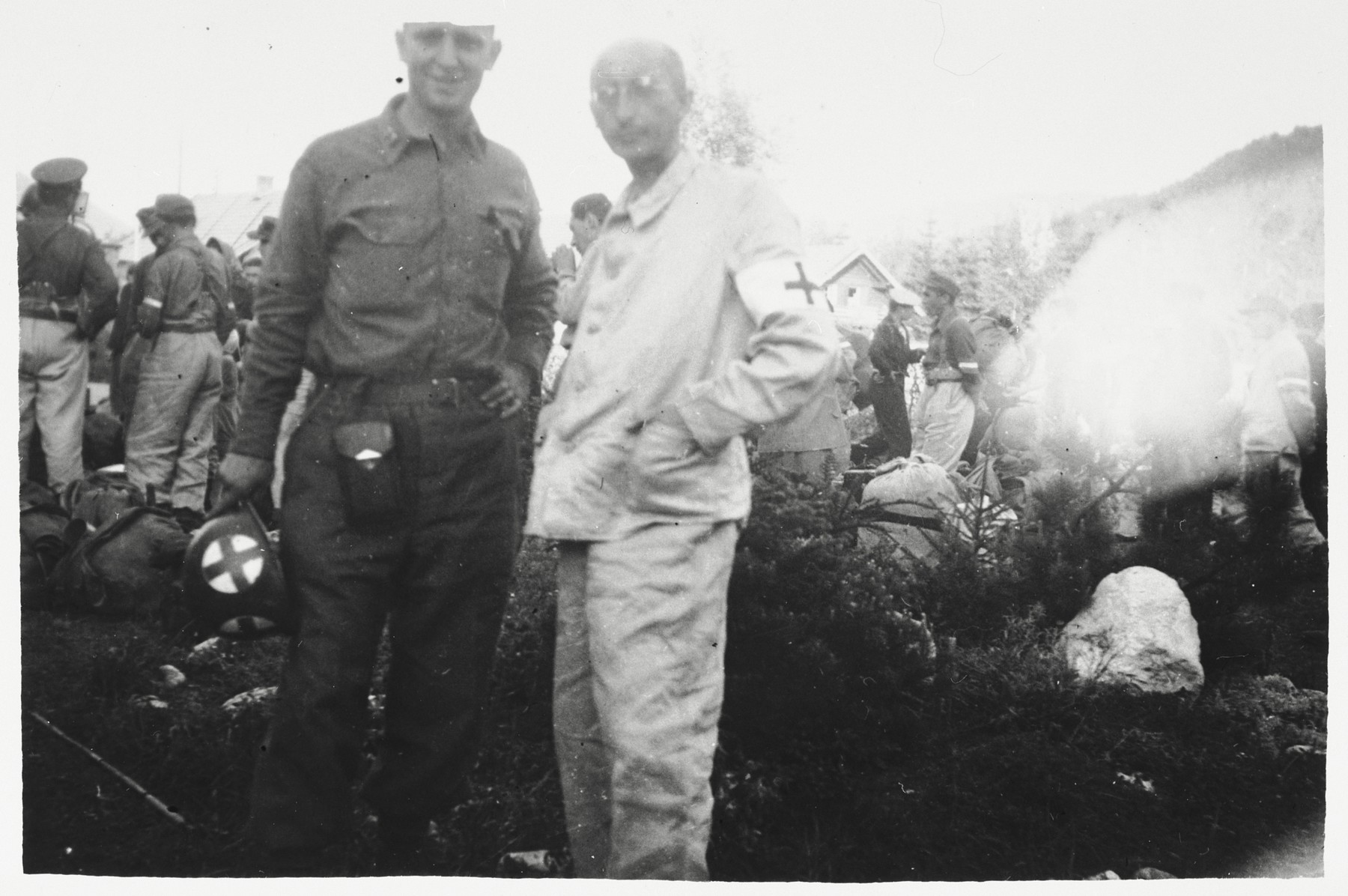 An American serviceman poses with the chief medical officer of a facility in Garmisch-Partenkirchen which provides medical care to survivors.  The chief medical officer is himself a liberated concentration camp prisoner.  The serviceman is Raymond Simokins.