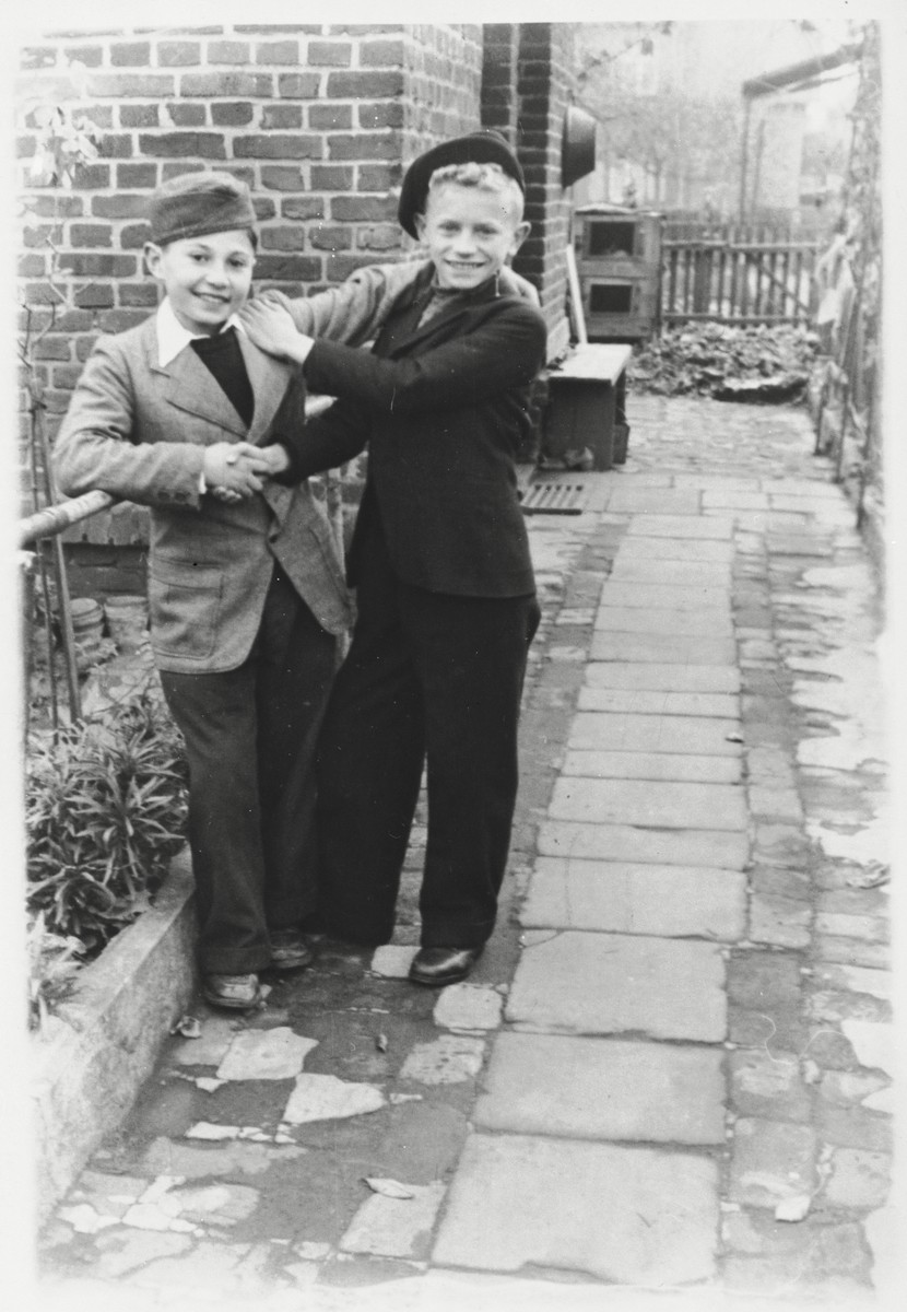 Szlomo Waks poses with a friend next to a railing in the Zeilsheim DP camp.