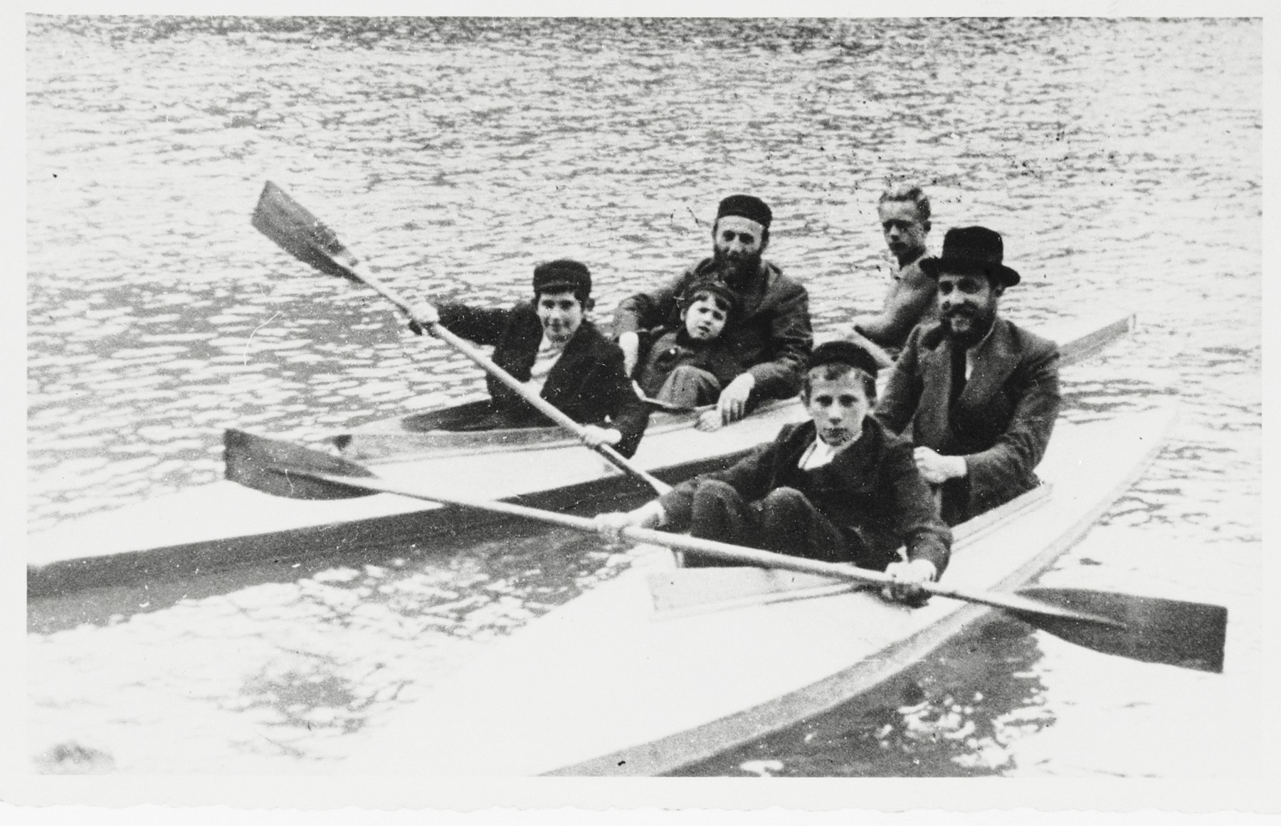 A group of religious Jews goes on a kayaking excursion.  Tsvi Majranc is seated in the middle of the rear kayak, holding a child.