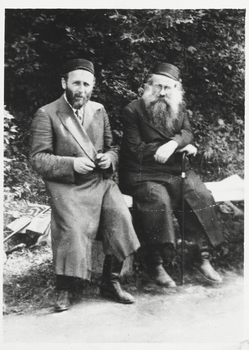 Two Hasidic men sit on a park bench in Lodz.  Tzvi Majranc is pictured on the left.