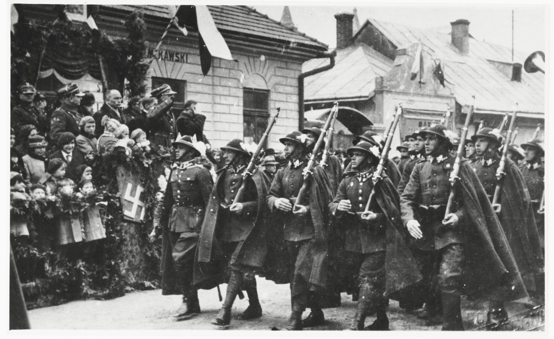 "Ceremonial Polish troops march down a street in Sanok, past a reviewing stand that included the Rabbi of Sanok, Tuvia Horowitz.  The symbol  on the stand that appears to be a swastika  may be a ""highlander cross,"" a  symbol popular in folk culture of the Polish mountainous regions."