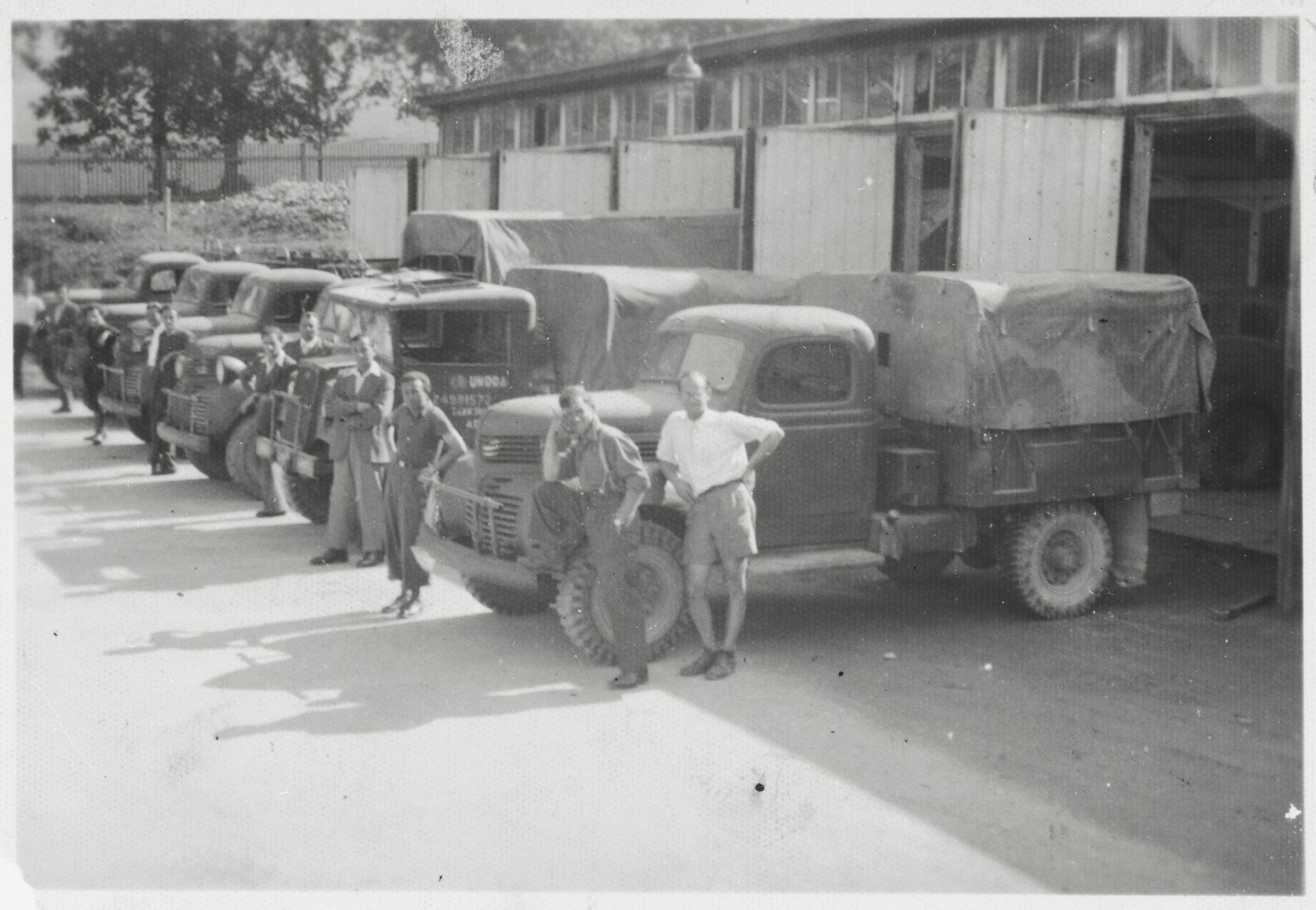 Bricha guides pose next to a row of covered trucks used to transport Jewish refugees from Hungary to Austria and Italy.